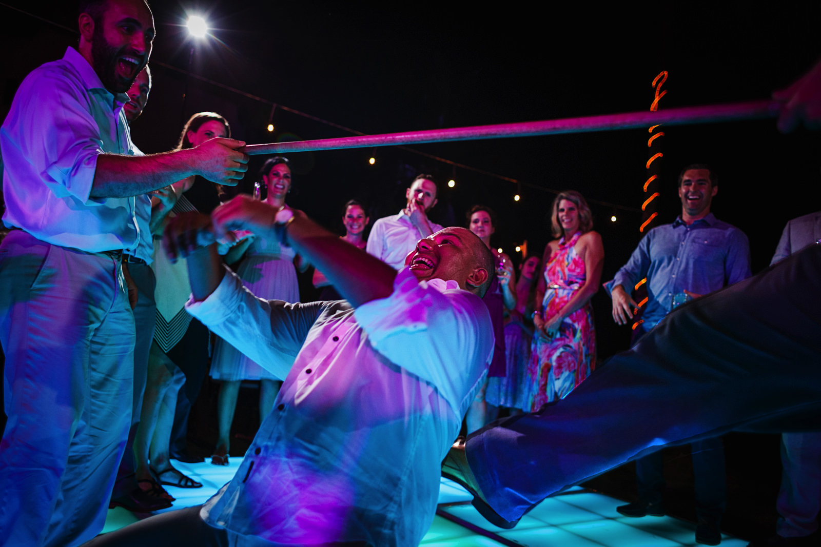 Guest almost falling playing limbo at wedding reception party