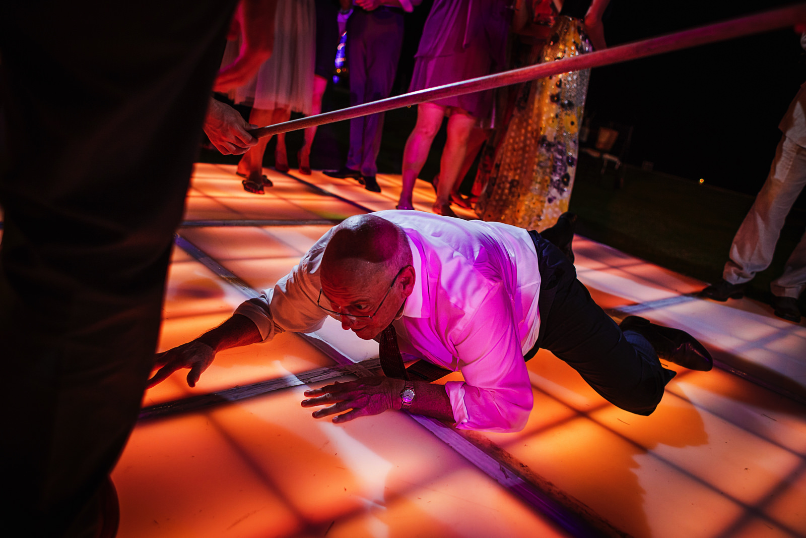 Father of the groom crawling under the limbo at wedding reception party