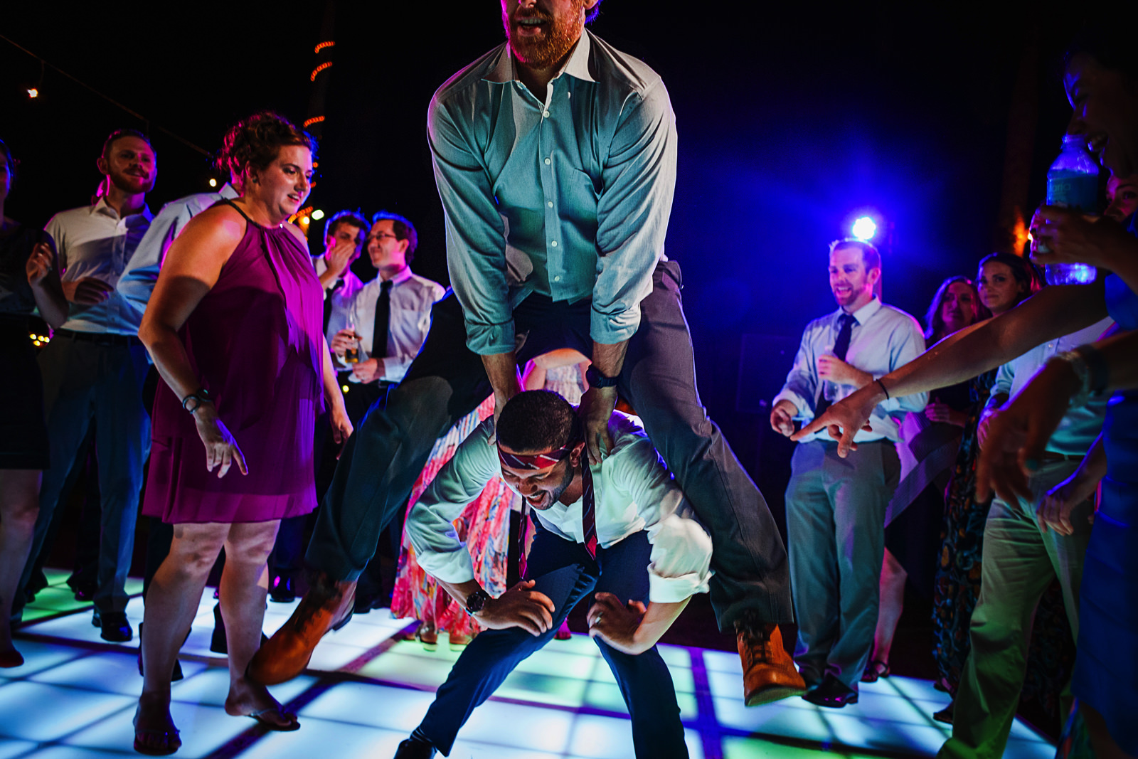 Guest jumping over other guest at wedding reception party