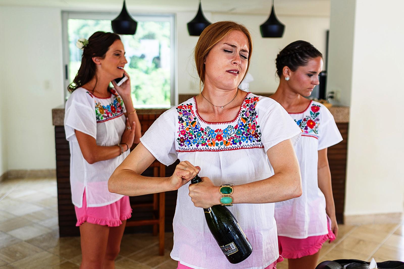 bridemaid opening the champagne - Eder Acevedo cancun los cabos vallarta wedding photographer
