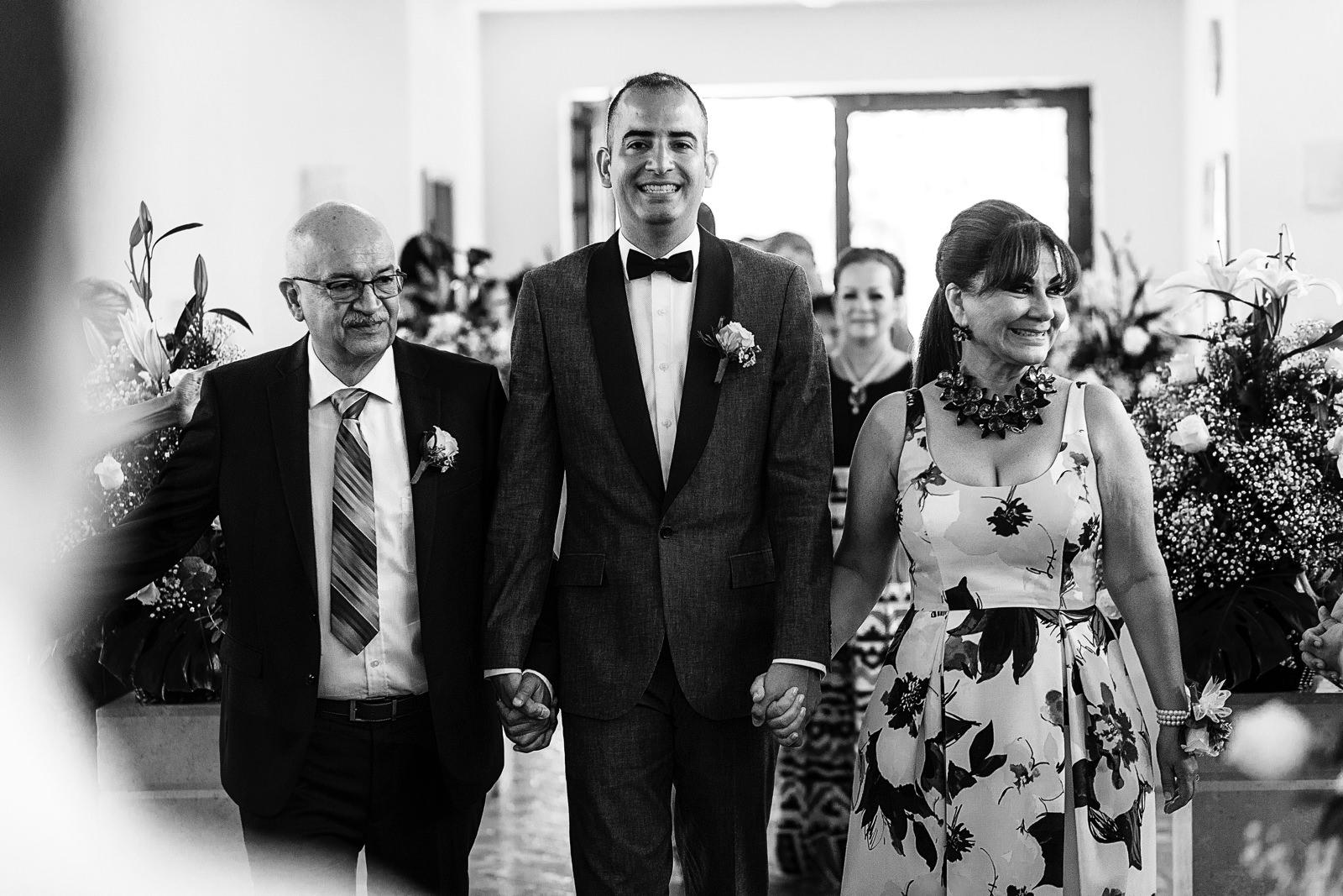 Novio y sus padres caminando hacia el altar para comenzar ceremonia religiosa de boda