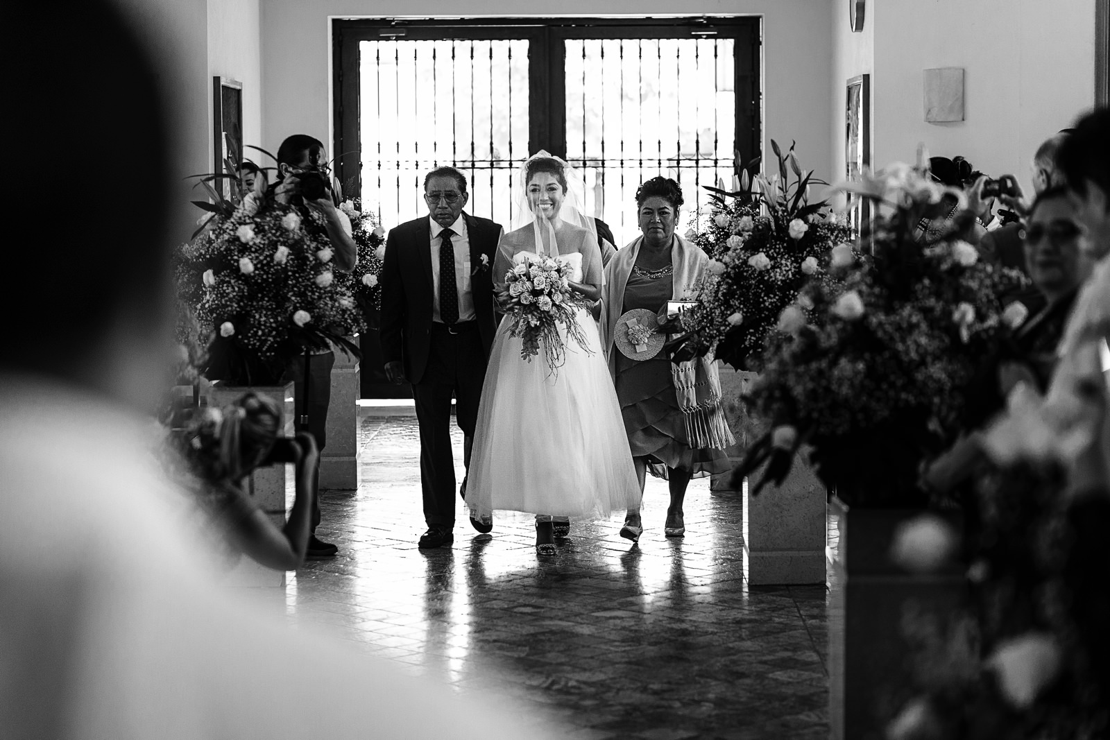 Novia sonriente caminando hacia el altar con sus padres a los lados en el día de su boda