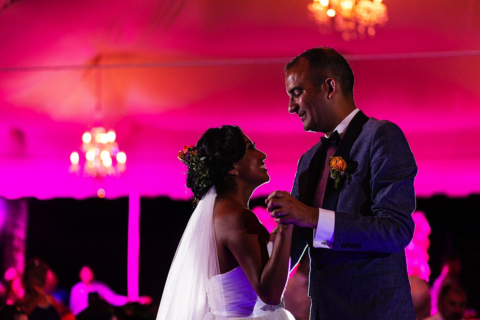 Primer baile de la pareja de novios bajo una carpa iluminada de color rosado