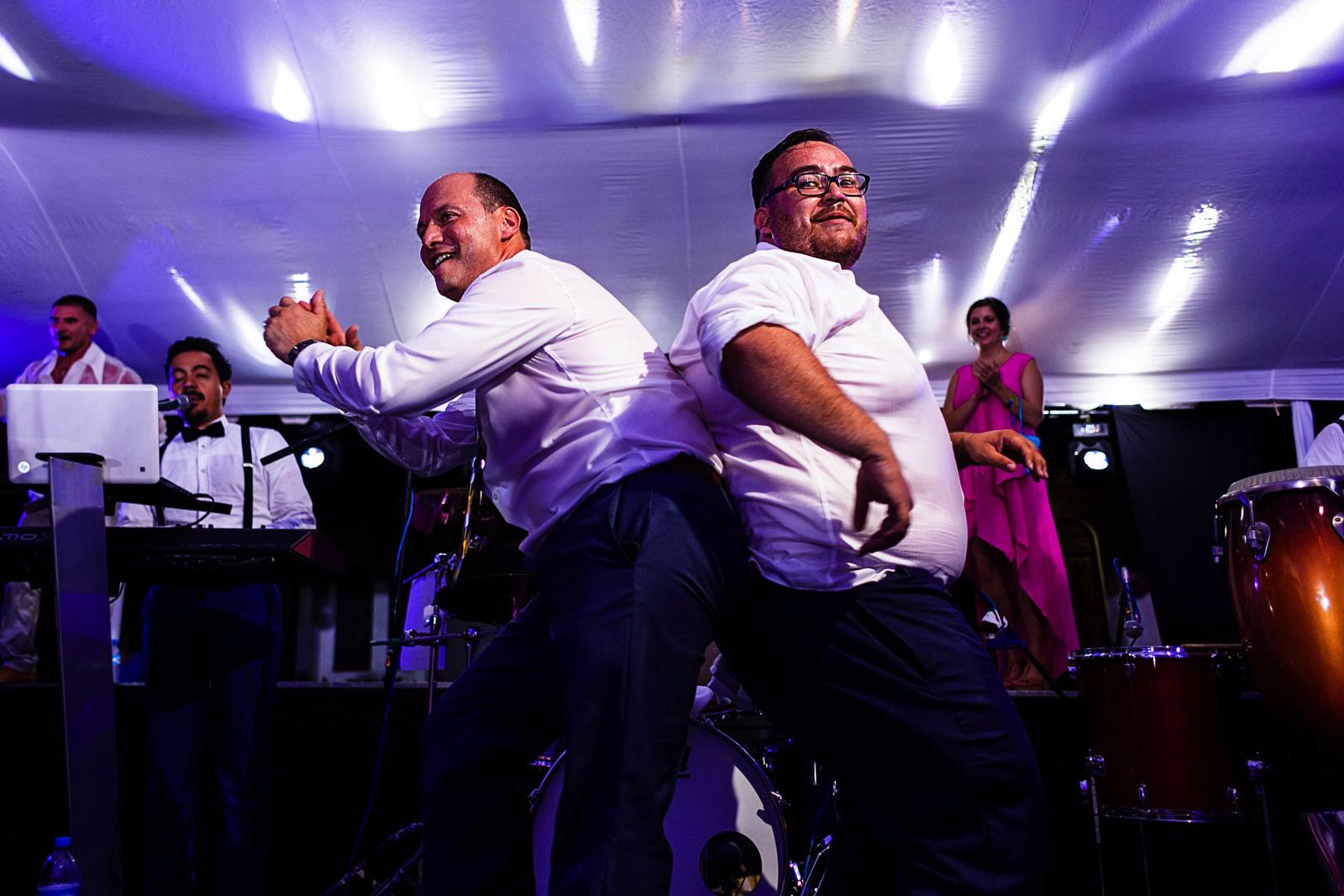 Dos hombres concursan bailando en el escenario junto a la banda musical