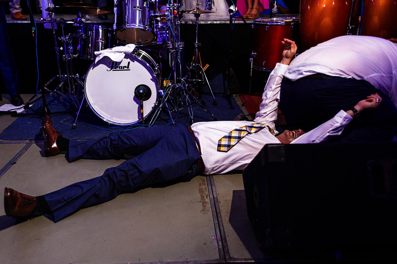 Un invitado acostado de espalda al piso del escenario durante un concurso de baile, tiene el trasero de otro concursante en su cara, en la fiesta del día de boda
