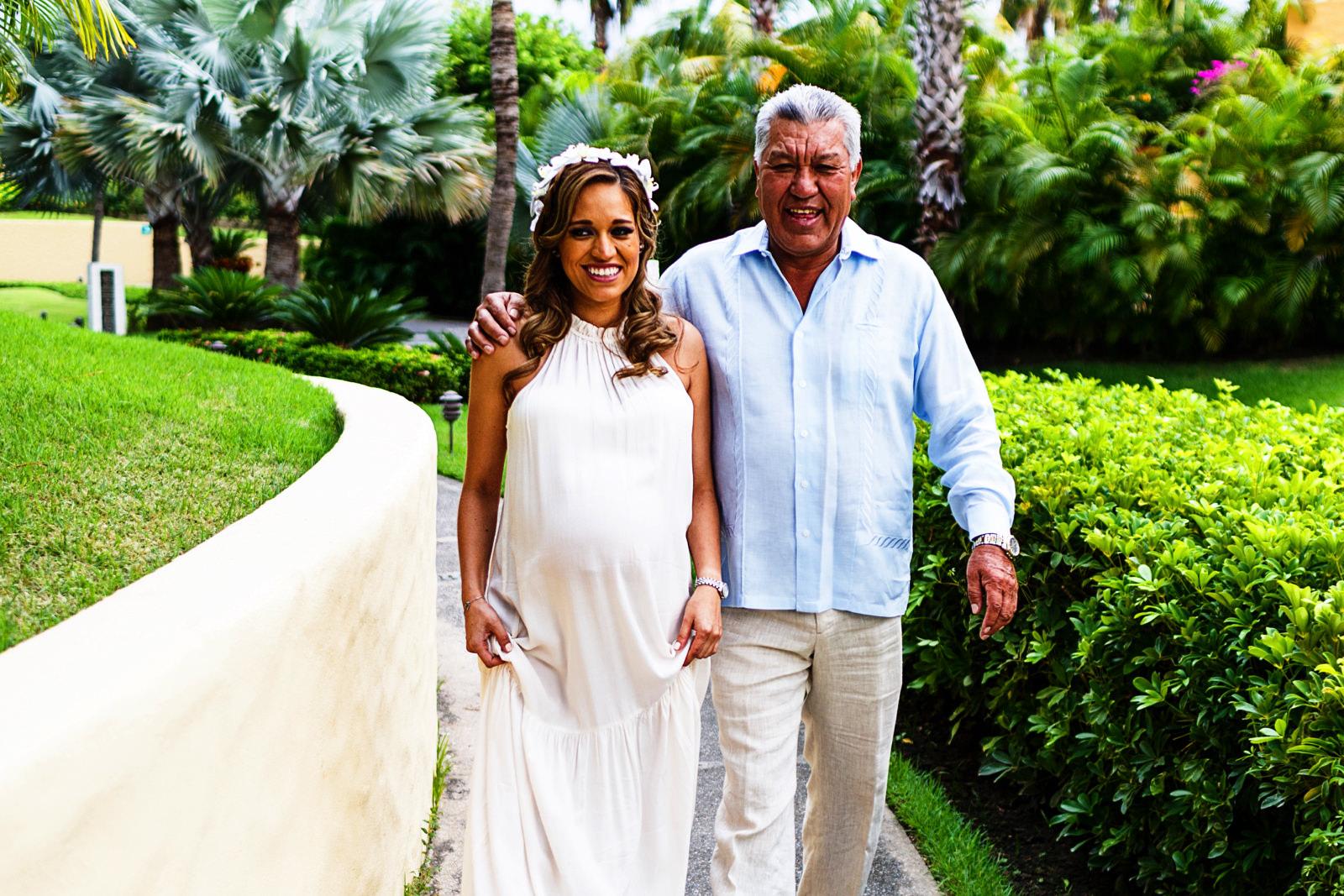 Novia y su papá caminando hacia la playa para dar inicio a la ceremonia