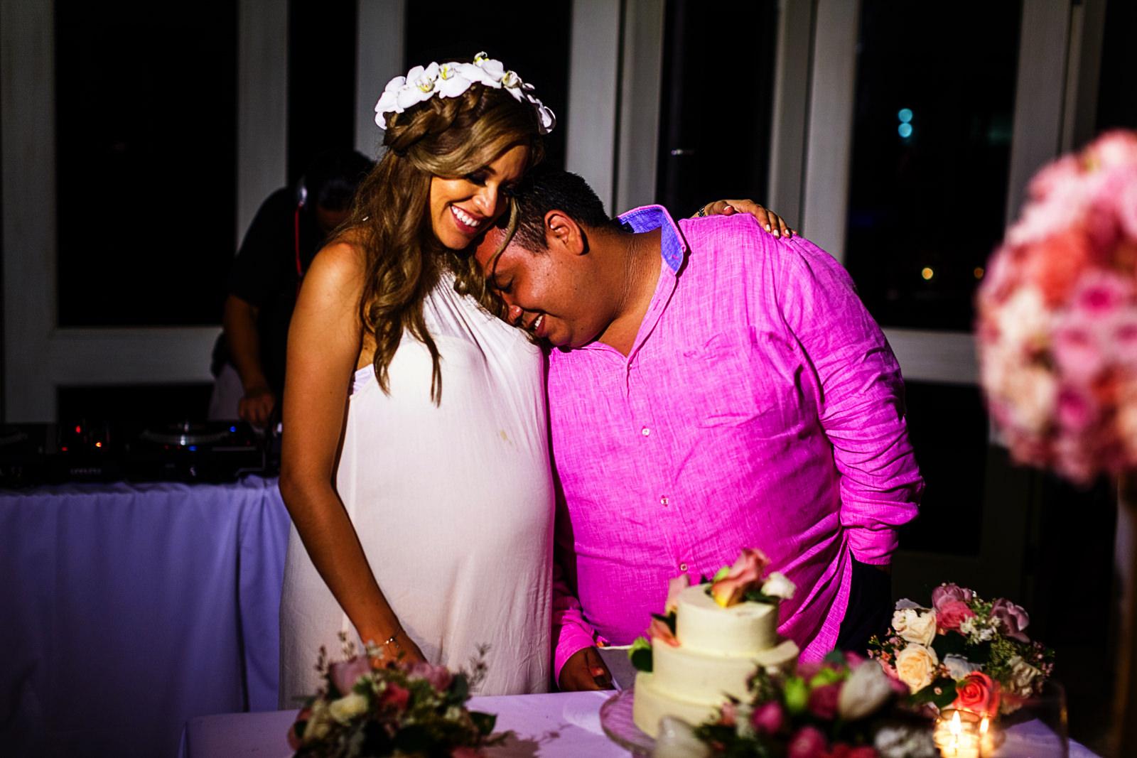 Novio se recarga en el hombro de su ahora esposa antes de cortar el pastel de bodas