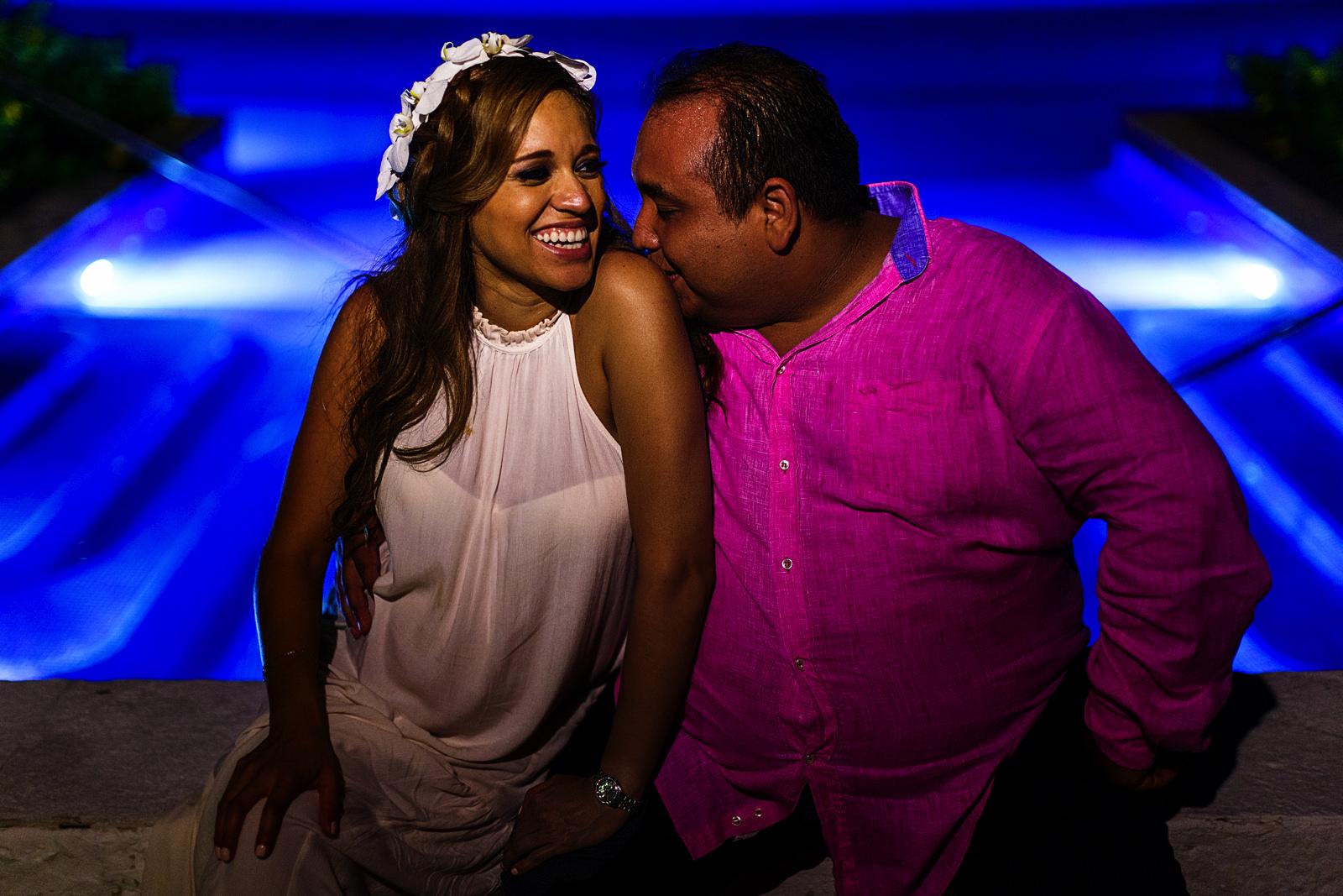 Novio besando el hombro de su esposa sentados en la alberca del St Regis Punta Mita