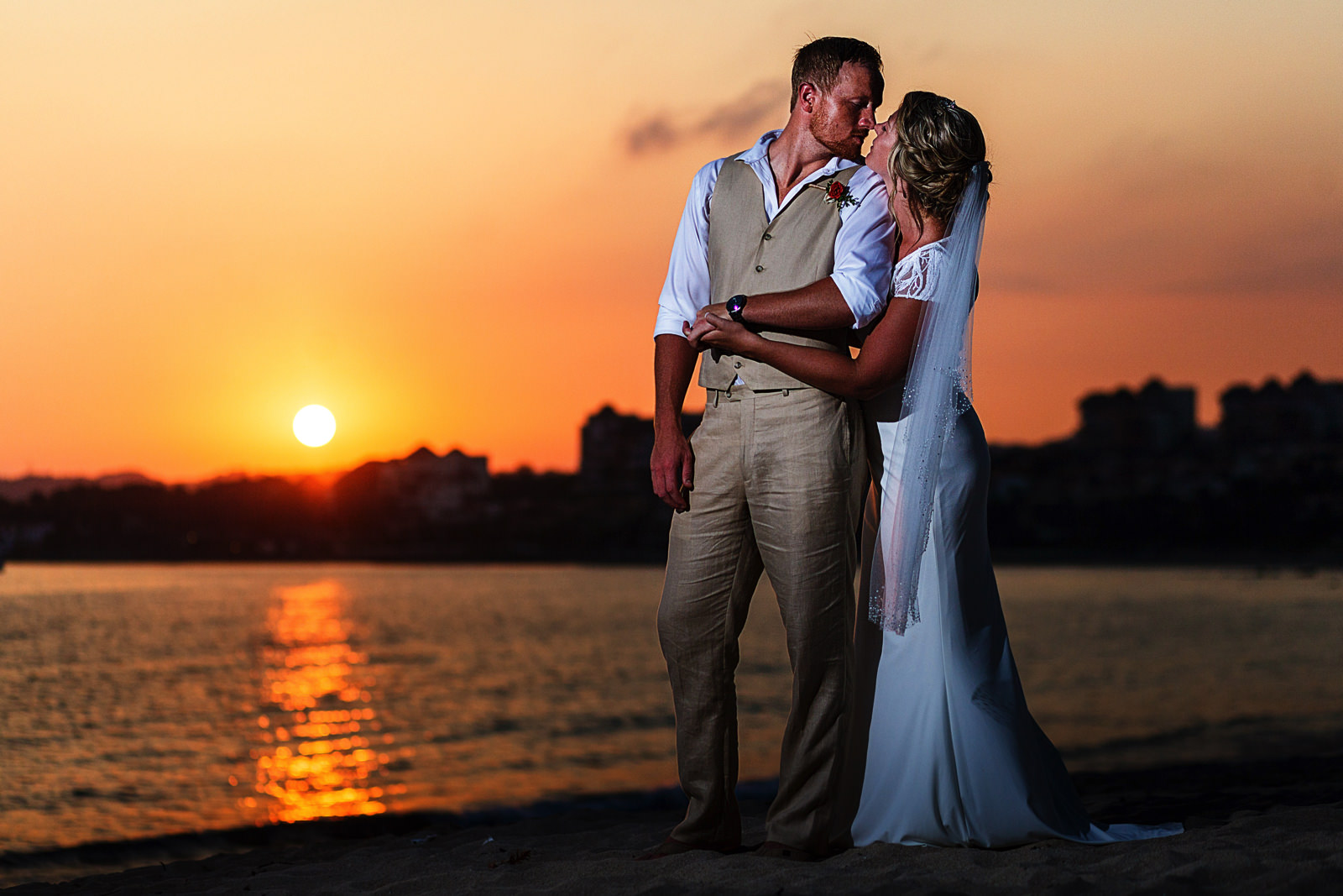 Groom and bride about to kiss on the beach at Bucerias Nayarit Mexico, sun setting behind them