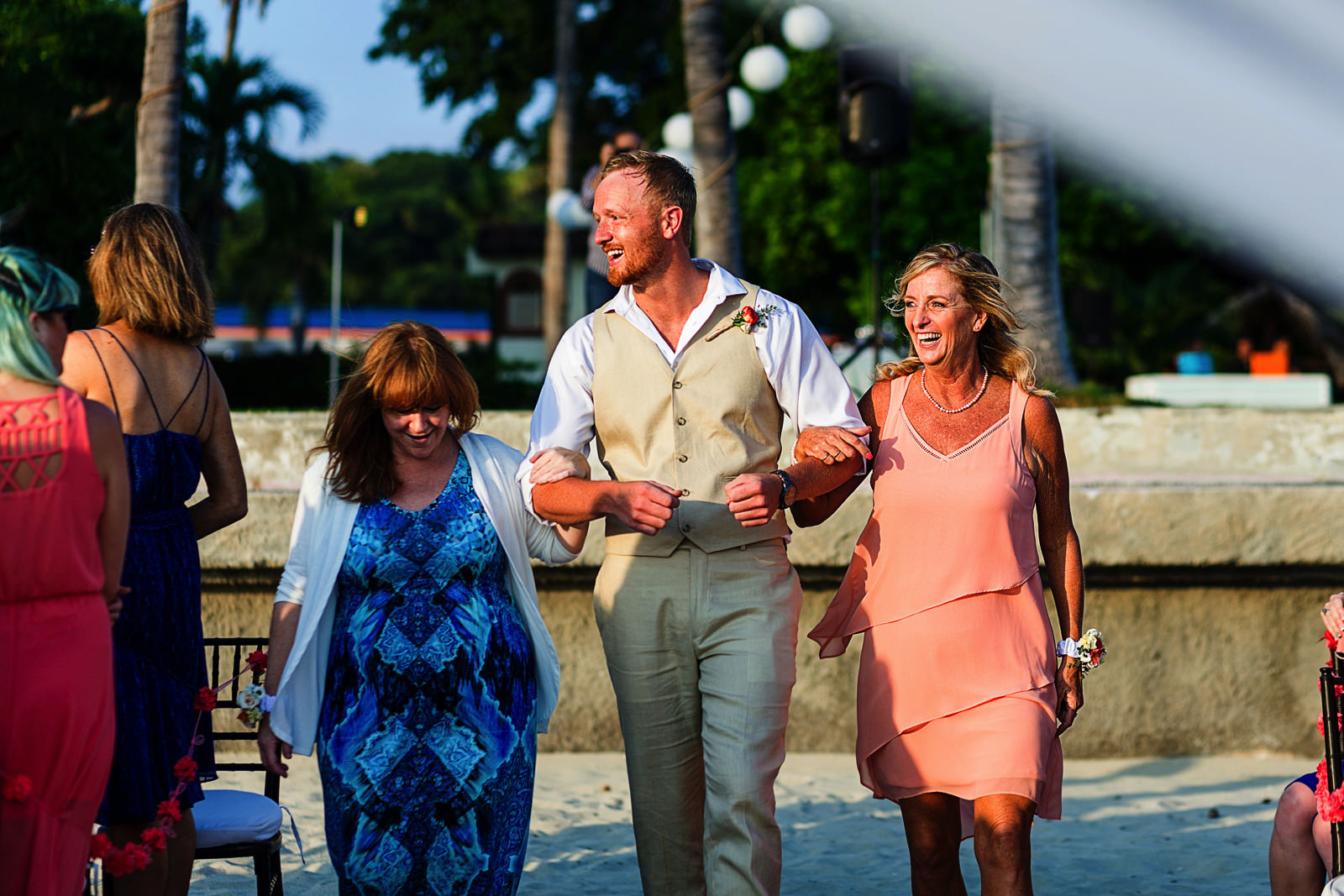 Groom walking down the aisle with both moms