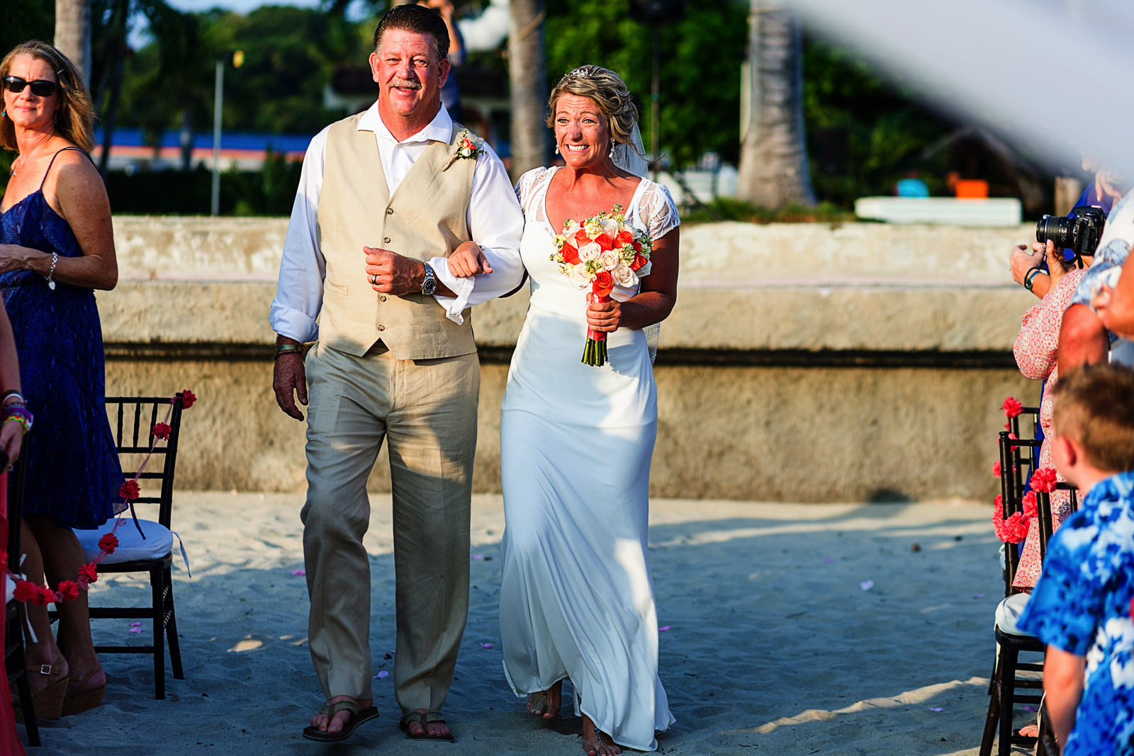 Dad and bride walking down the aisle, bride reacts with big smile to guests