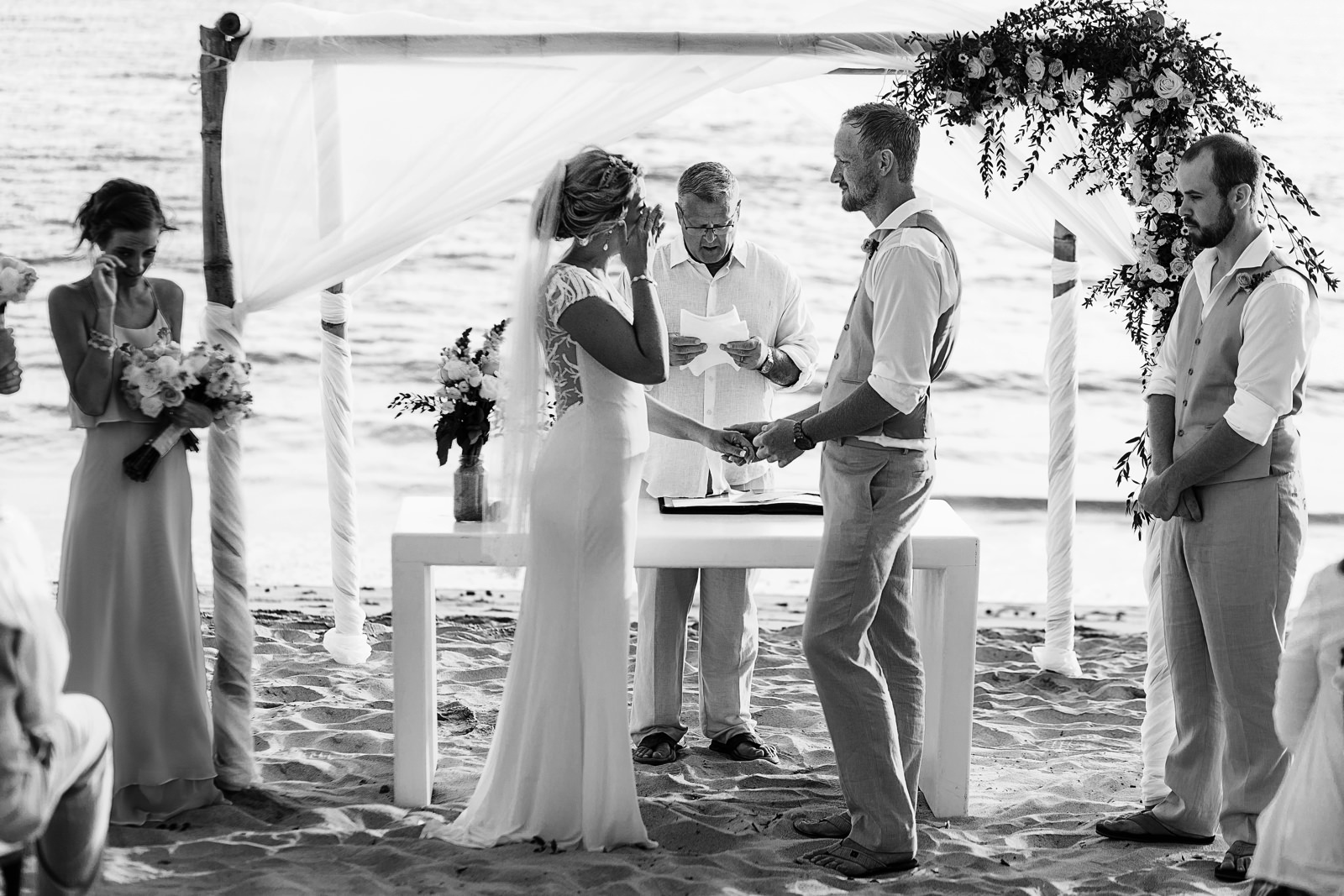 Bride and sister crying during wedding ceremony on the beach