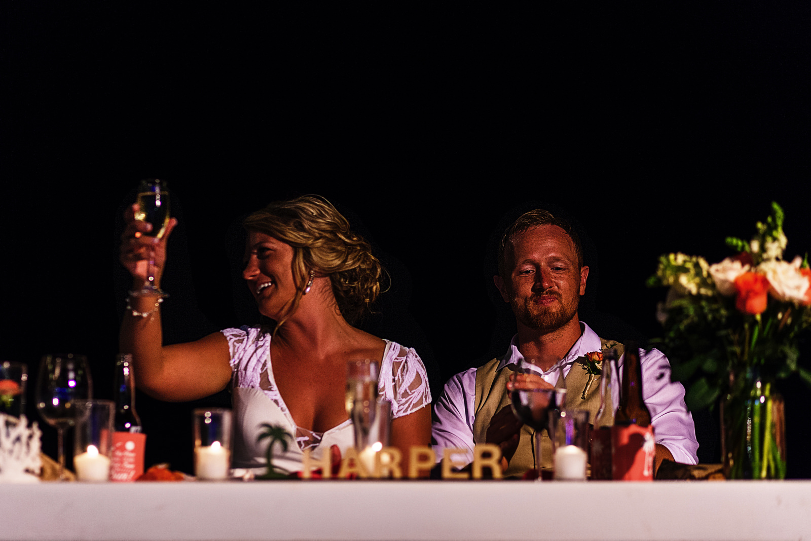 Bride raising a glass of champagne during best man's speech