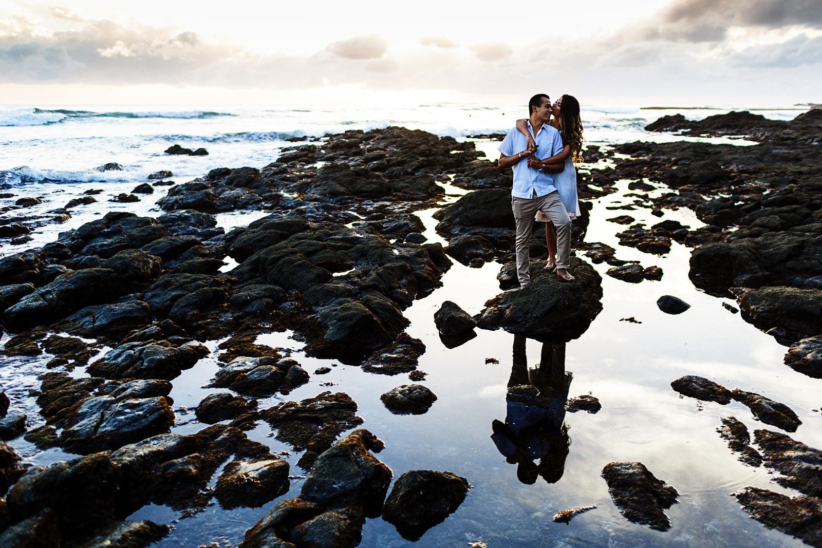 Pareja parada en una roca entre el agua reflejante en la playa La Lancha, Riviera Nayarit, sesión casual