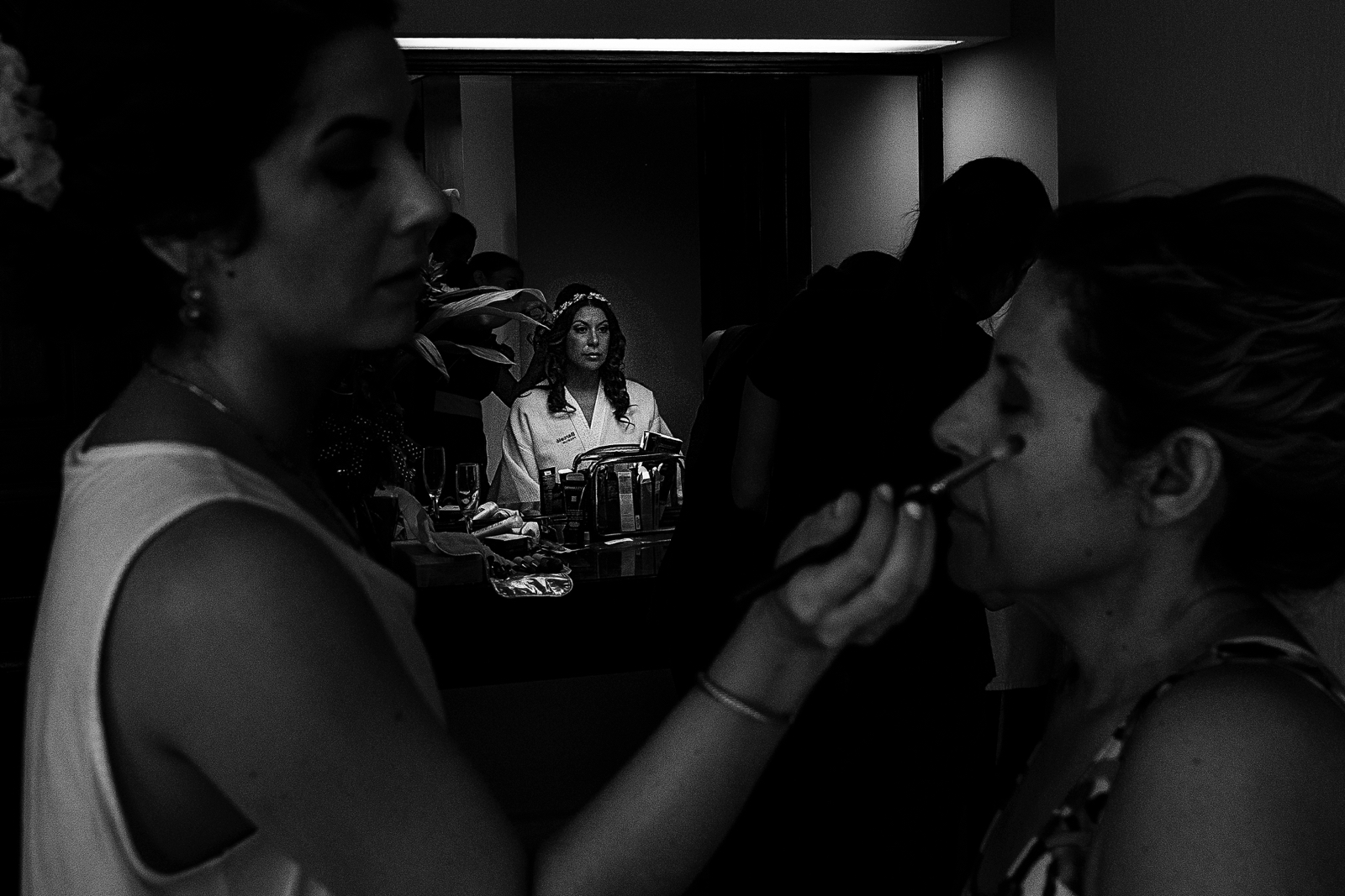 Bride having her make up done in front of the mirror while the sister does her mom make up