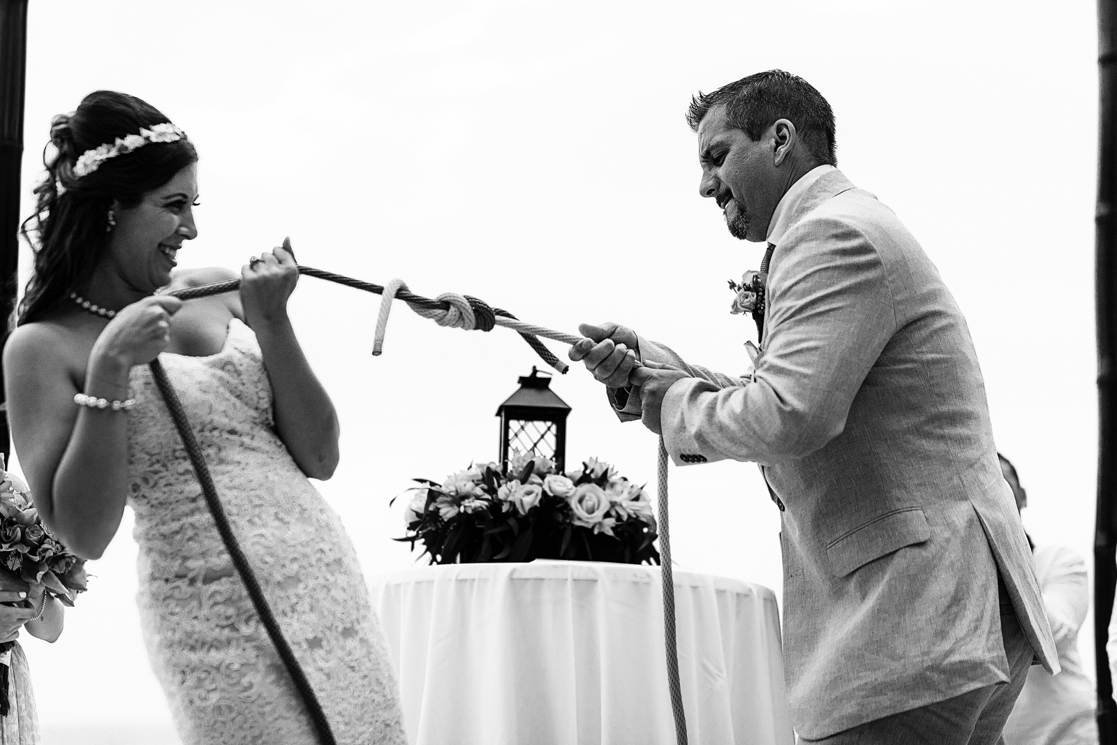 Groom and bride testing the strength of the knot they made as part of the wedding ceremony