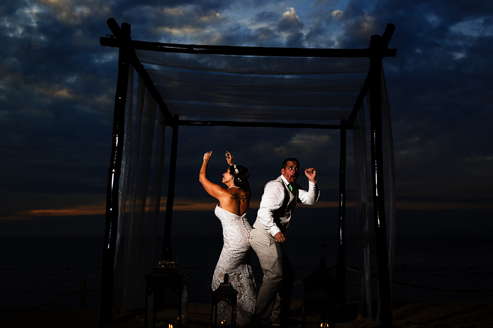Portrait of the couple dancing under the chuppah at sunset on the beach