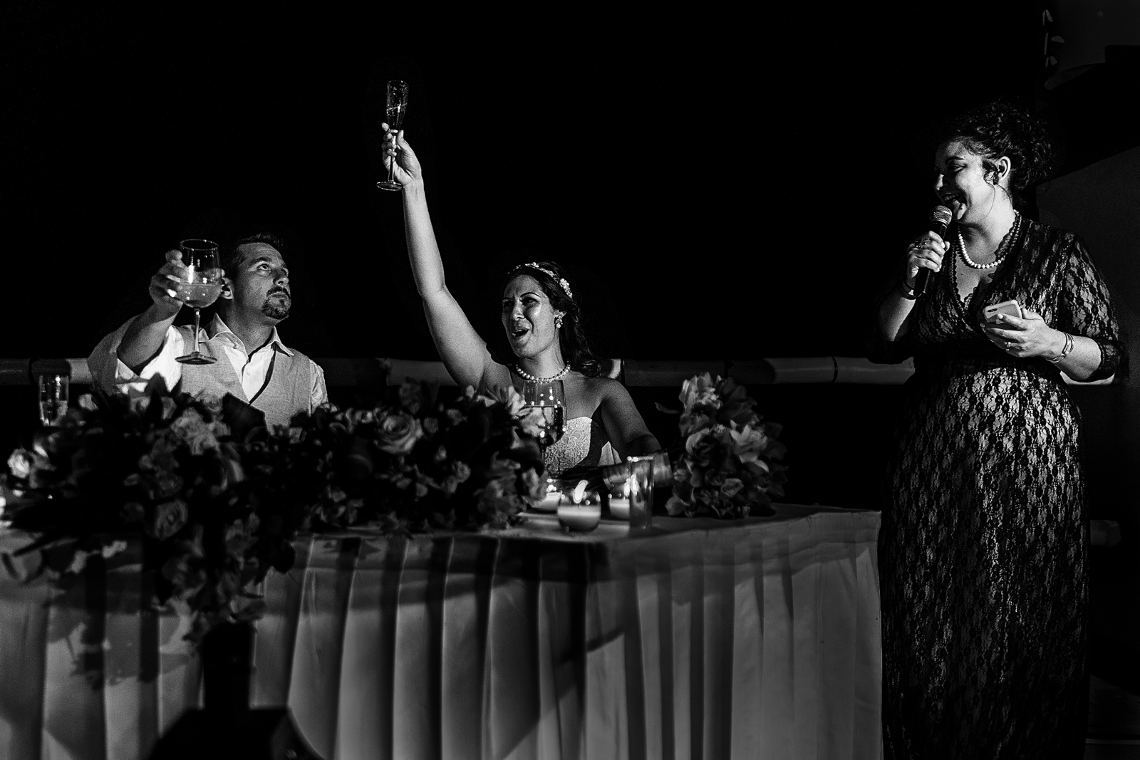 Maid of honor giving a speech, groom and bride raising their champagne glasses