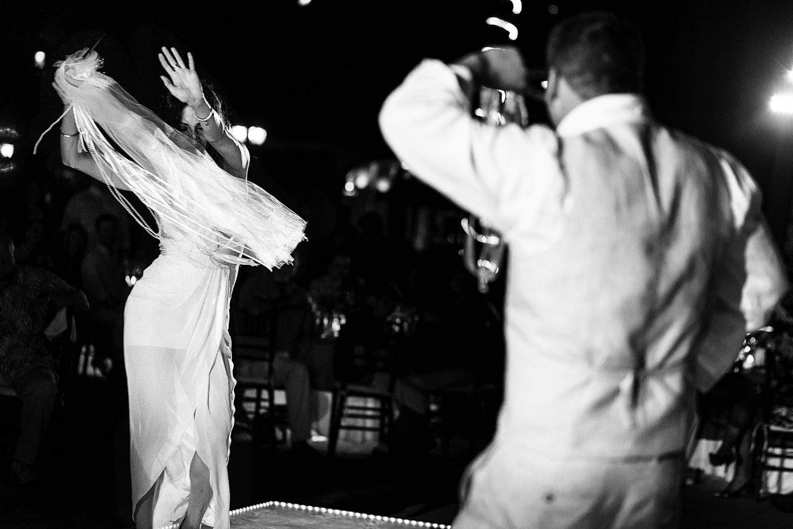 Wedding female guest dancing during traditional Persian dance for the groom to recover the wedding cake knife