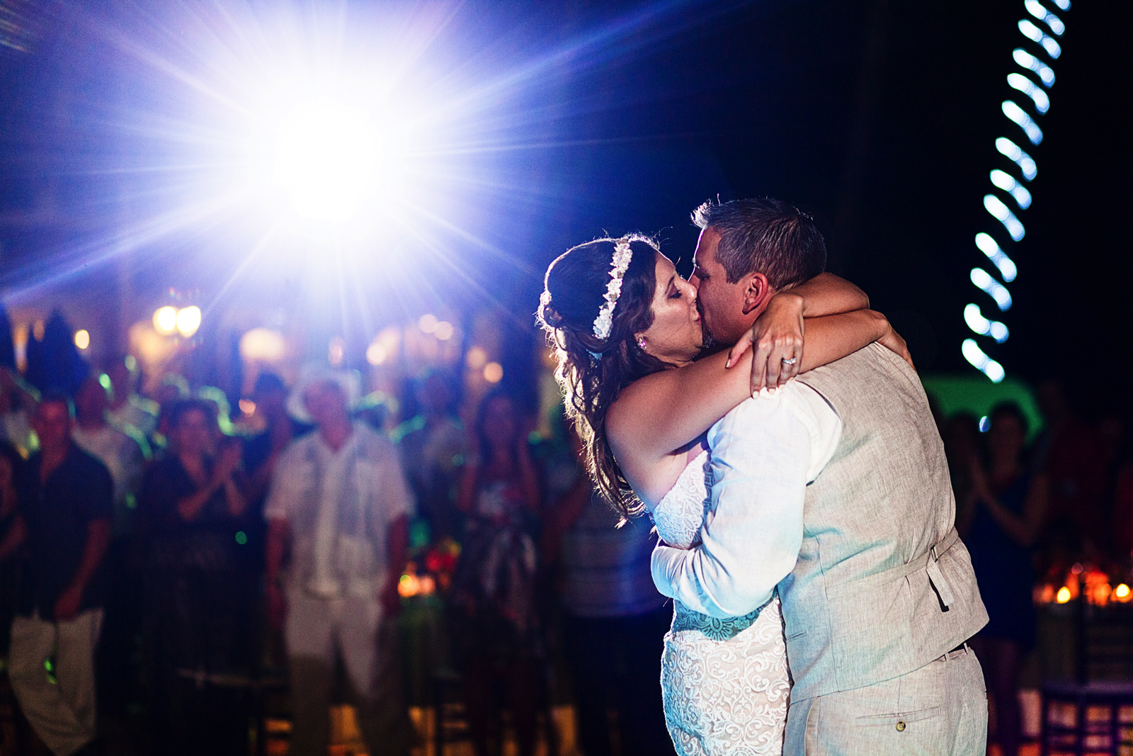 Groom and bride kissing on the dance floor during their entrance to the wedding reception