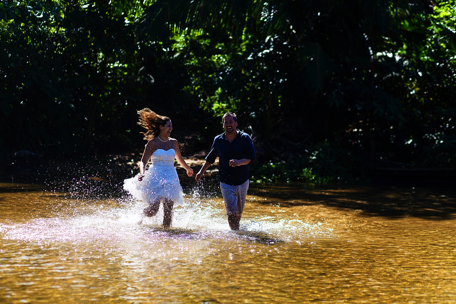 Groom and bride running in the river during their trash-the-dress photo session