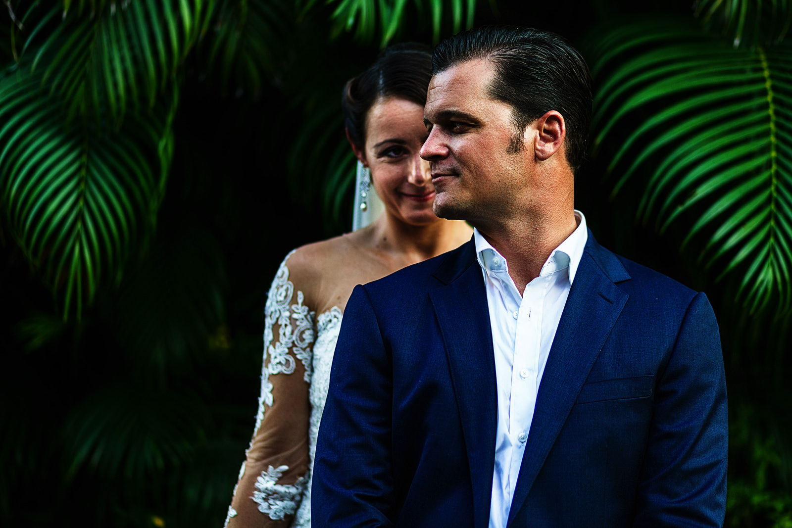 Portrait of the couple standing in front of palm leaves, bride behind the groom