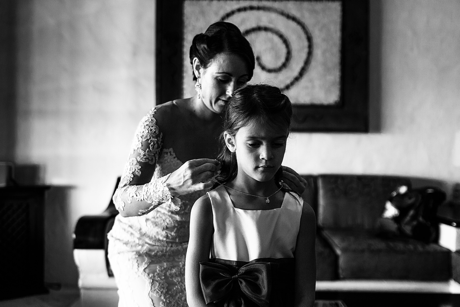 Bride putting a necklace into a little girl