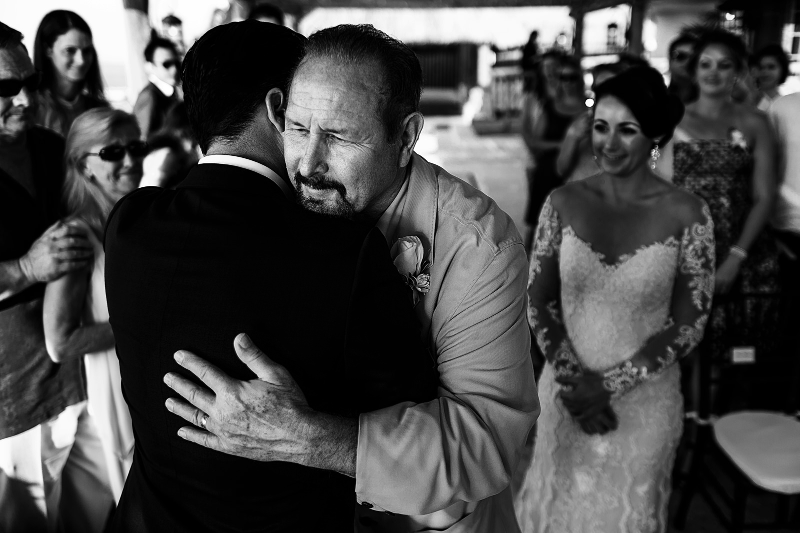 Father of the bride hugging the groom at the altar