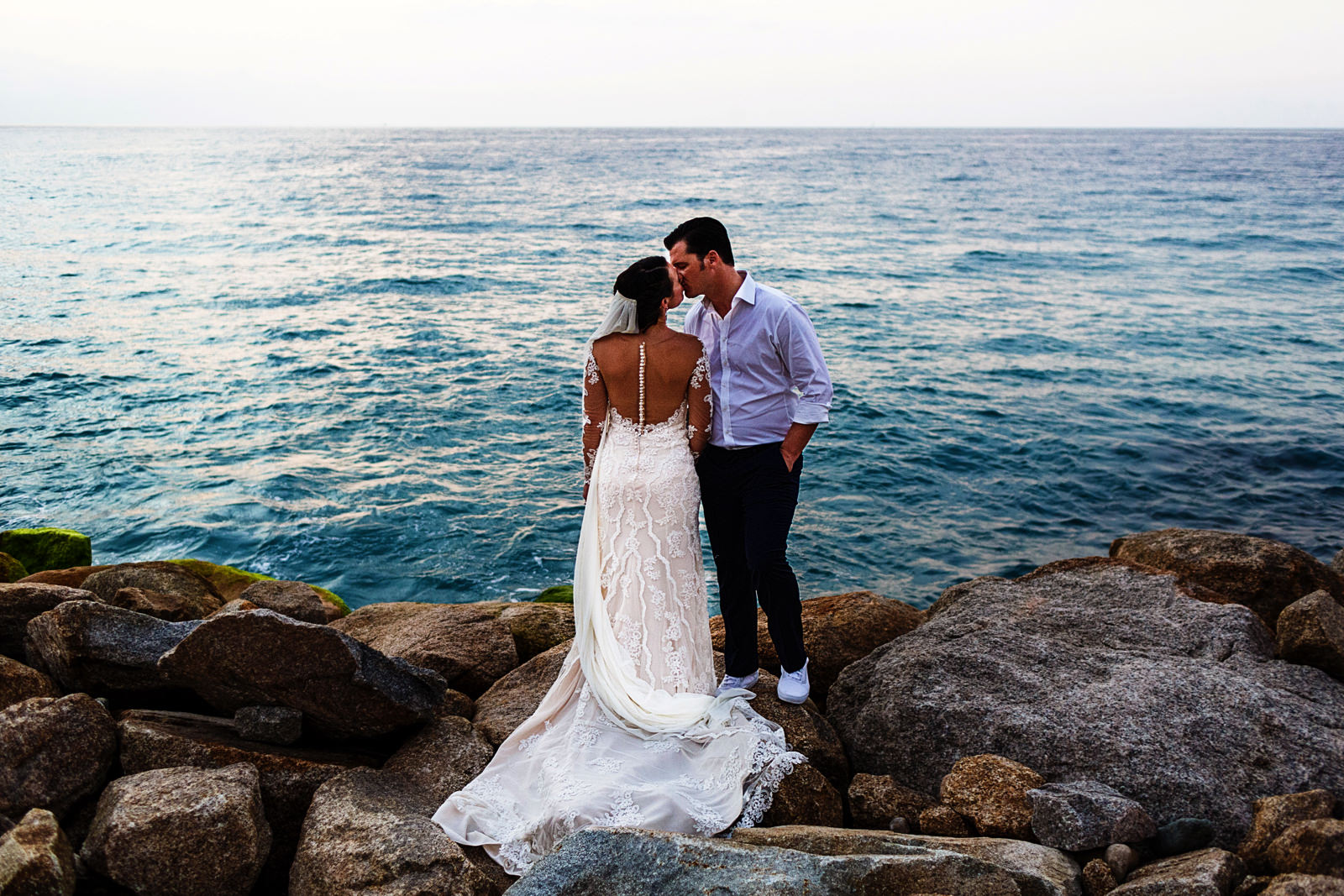 Groom and bride standing on a pile of rocs kissing with the ocean on their background