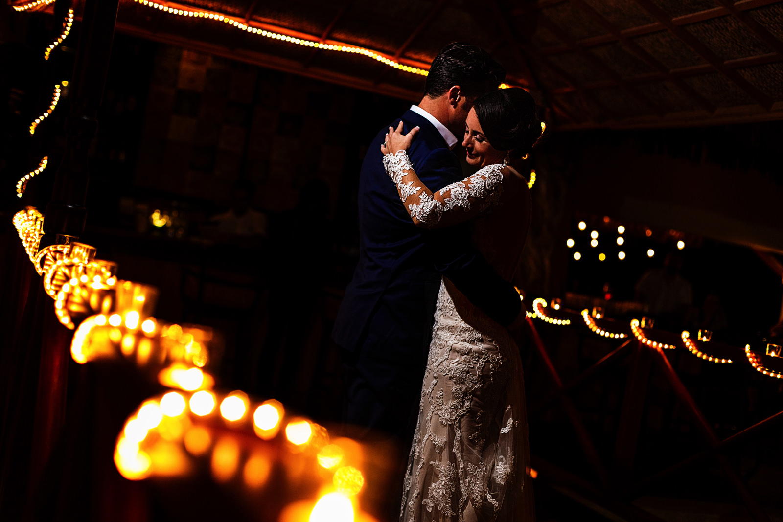Groom and bride during their first dance on the beautifully lit  Playa Fiesta's bridge