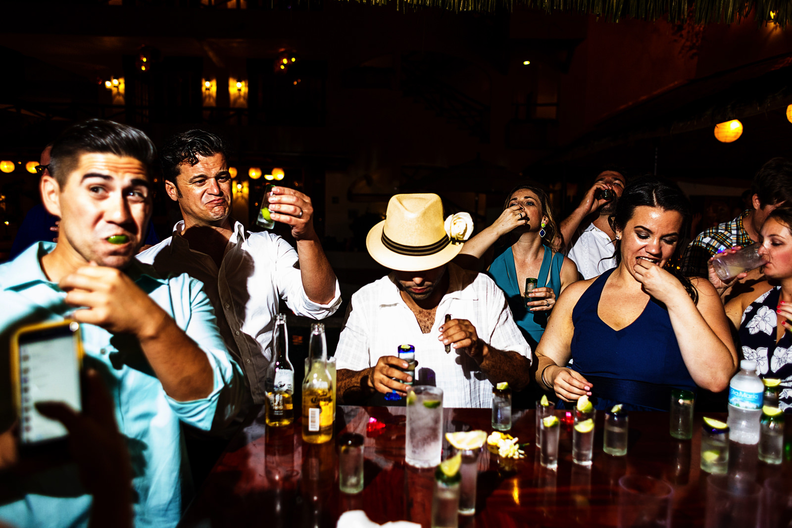 Several wedding guests having a tequila shot at the bar with the groom