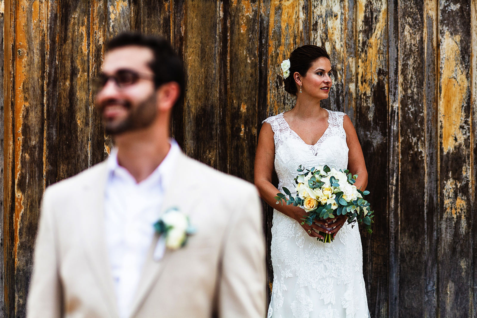 Portrait of a groom and bride on a door outside a tequila factory, groom in fore ground out of focus