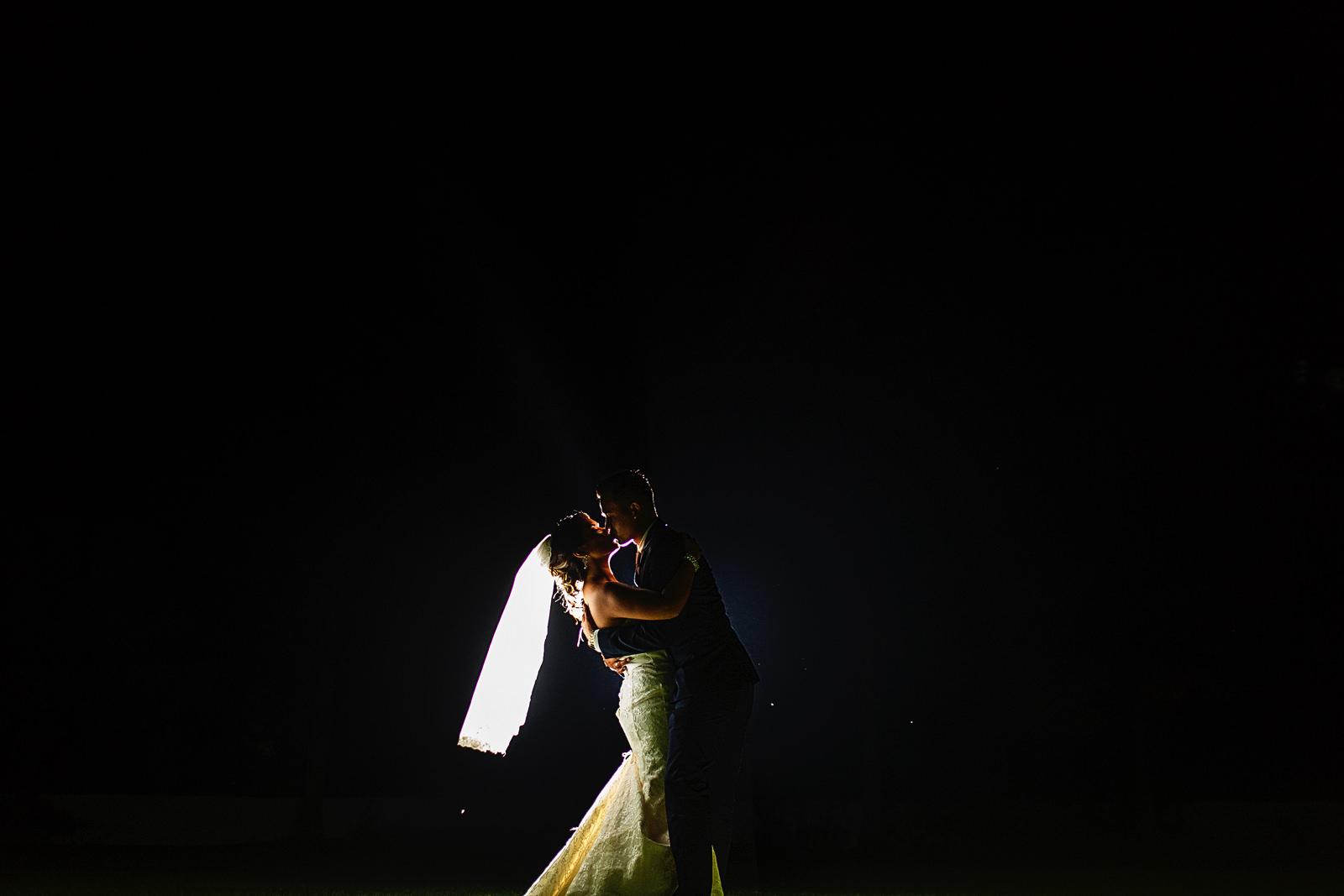 Pareja besándose en la oscuridad después de su ceremonia de bodas en su sesión de retratos