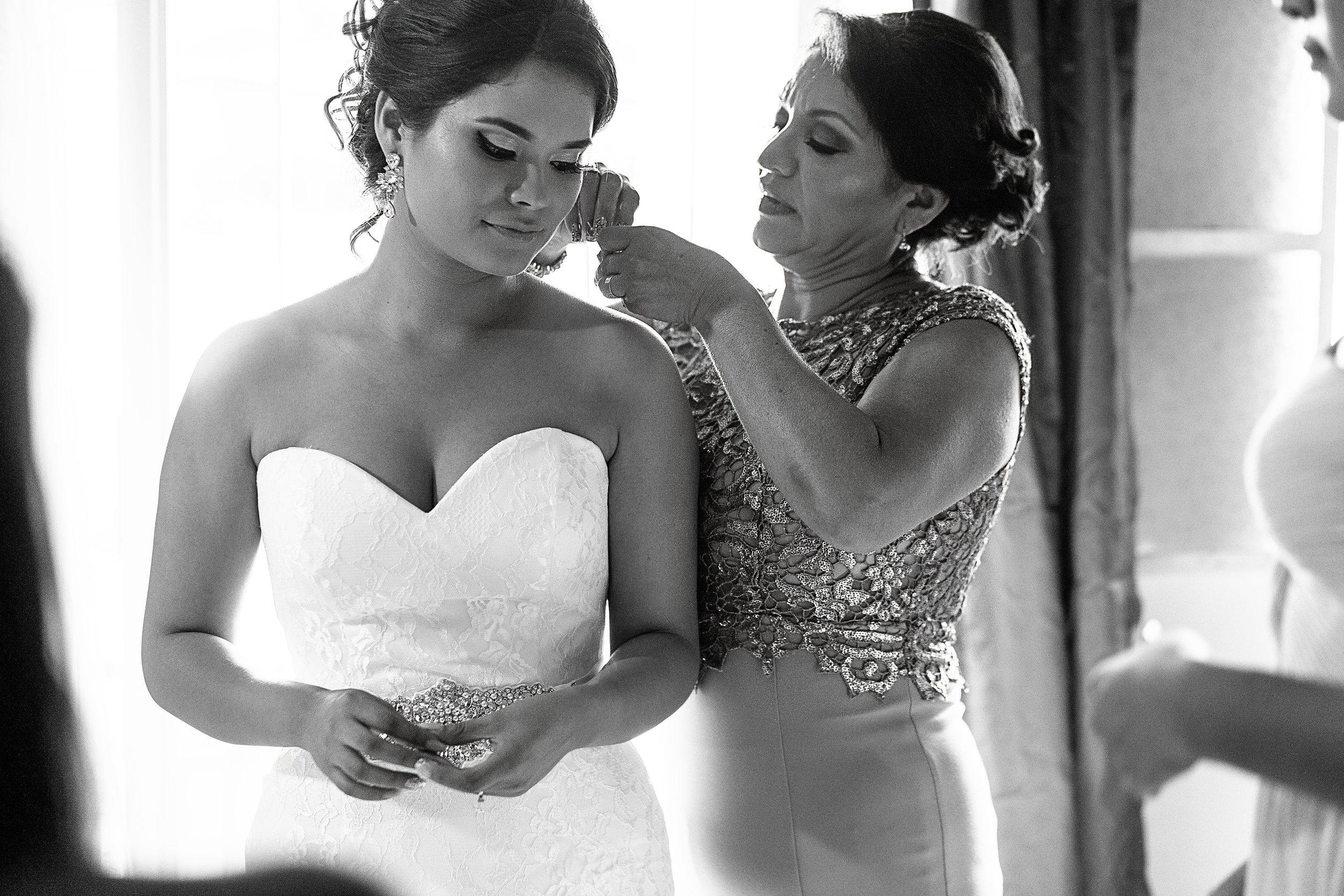 Mamá de la novia poniéndole los aretes a la novia durante los preparativos