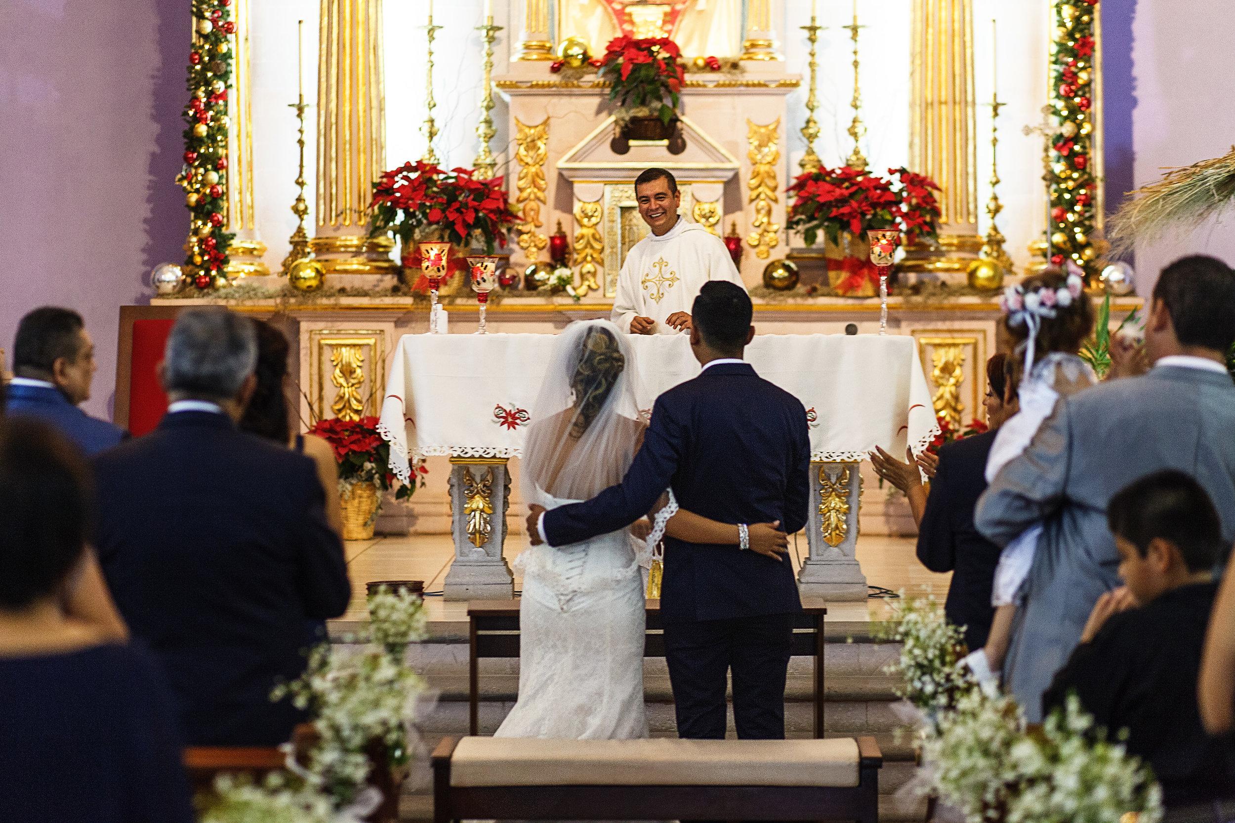 El sacerdote de la iglesia ríe en su sermon frente a la pareja de recién casados que permanecen abrazados frente al altar