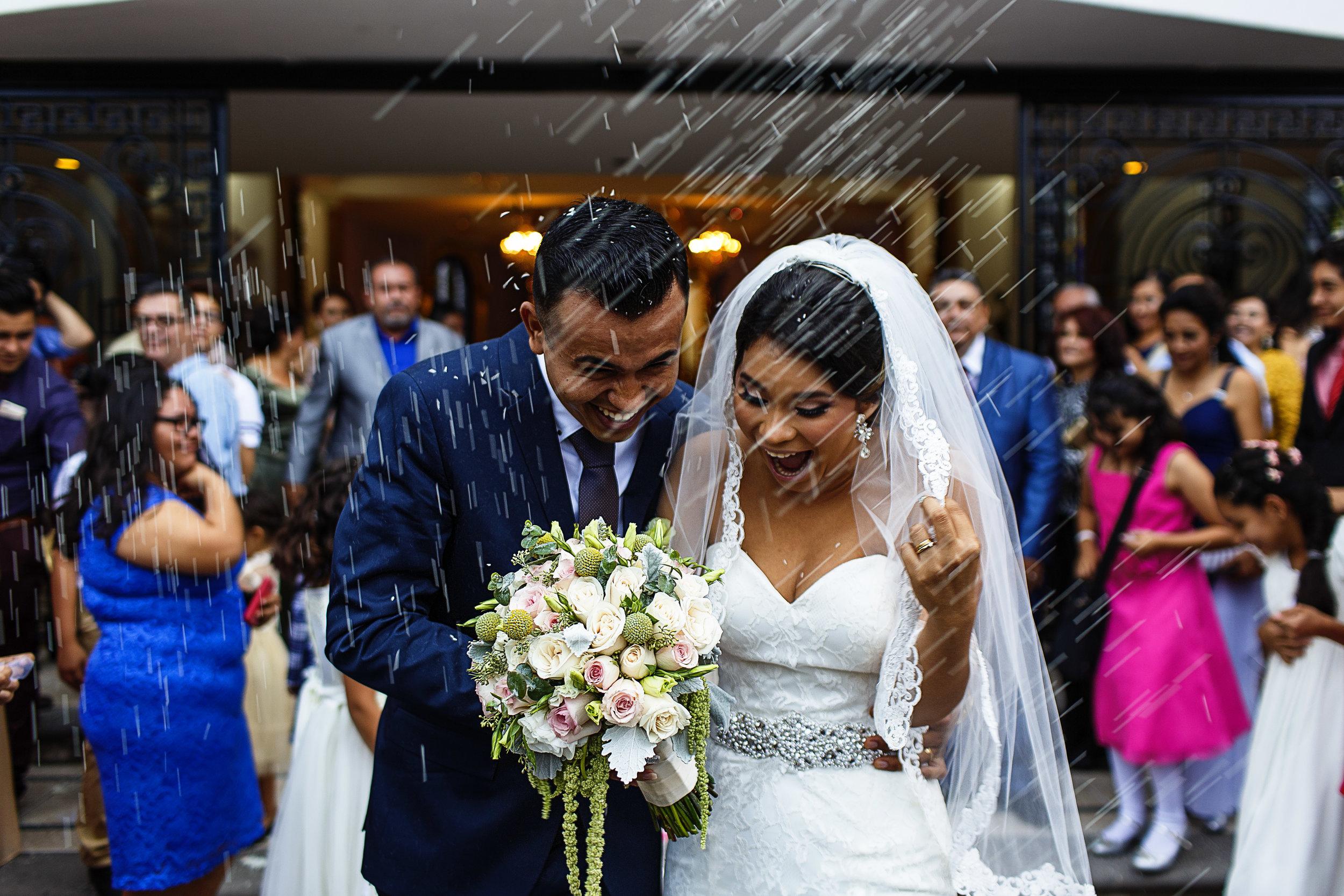 La feliz pareja reacciona a la lluvia de arroz al terminar su ceremonia religiosa de boda