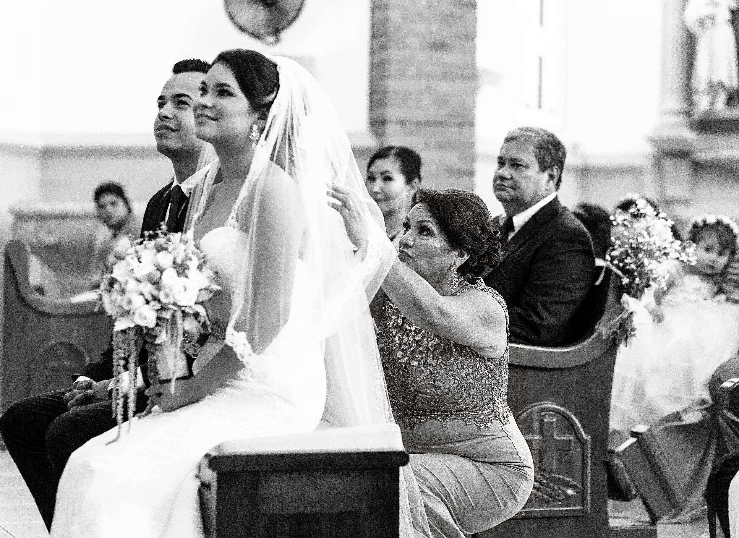 Madre de la novia reajustando el velo durante la ceremonia religiosa de la boda