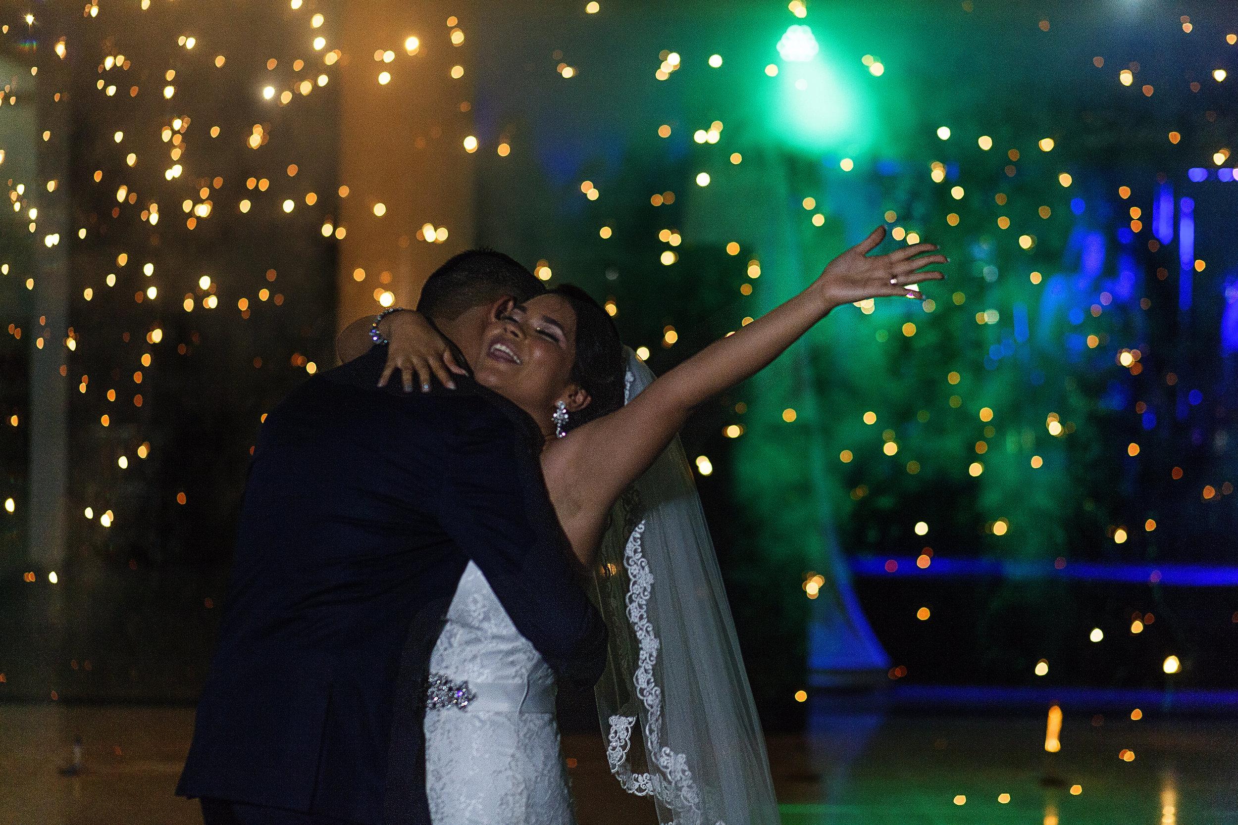 Novia sonríe y levanta su mano durante su primer baile como pareja casada, al fondo vemos el ultimo rastro de los chisperos
