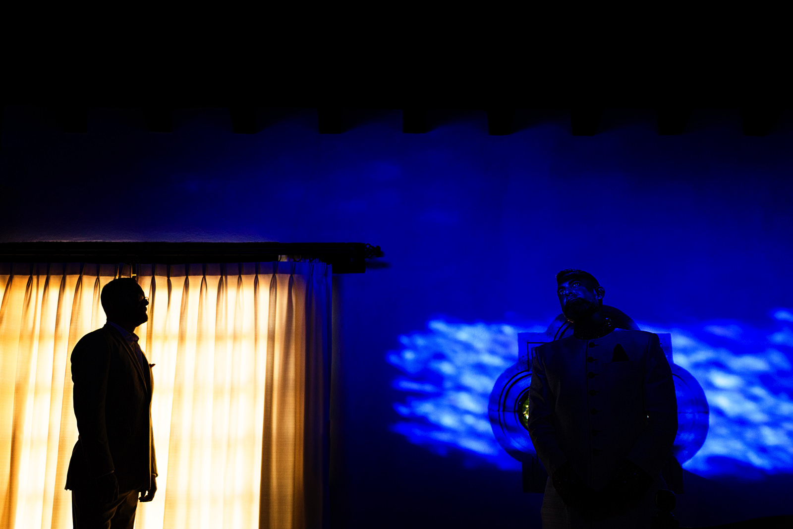 Gay couple's abstract portrait in blue and yellow with a silhouette of one man on a window and his husband on the blue spot