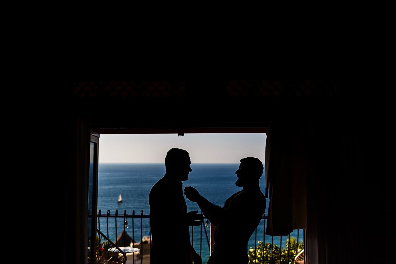 Silhouette of groom and best man getting ready for wedding ceremony
