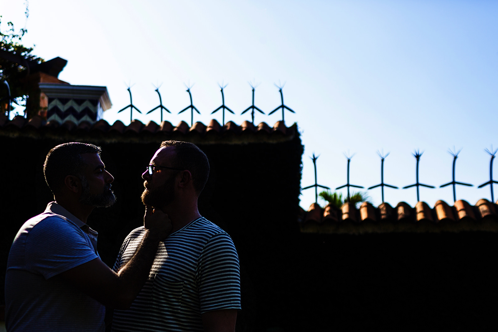Silhouette of a couple with light against a dark wall outside Casa Muni