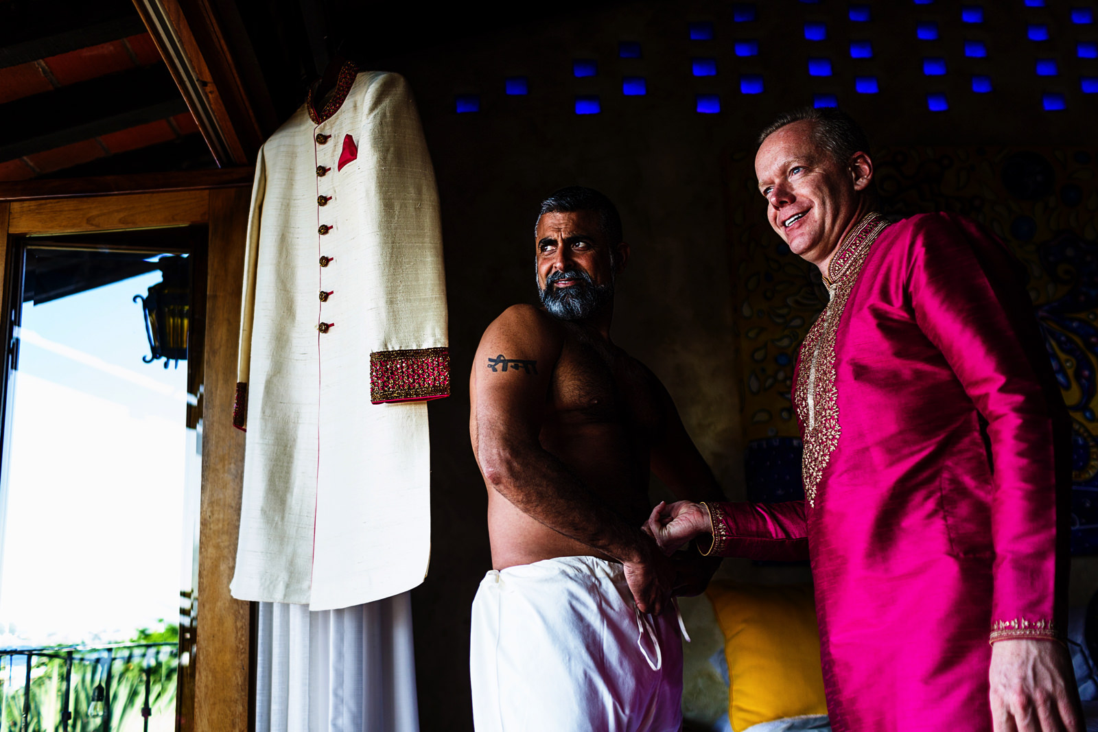 Groom and best man looking outside the window, the hindi attire is hanging on the window rack