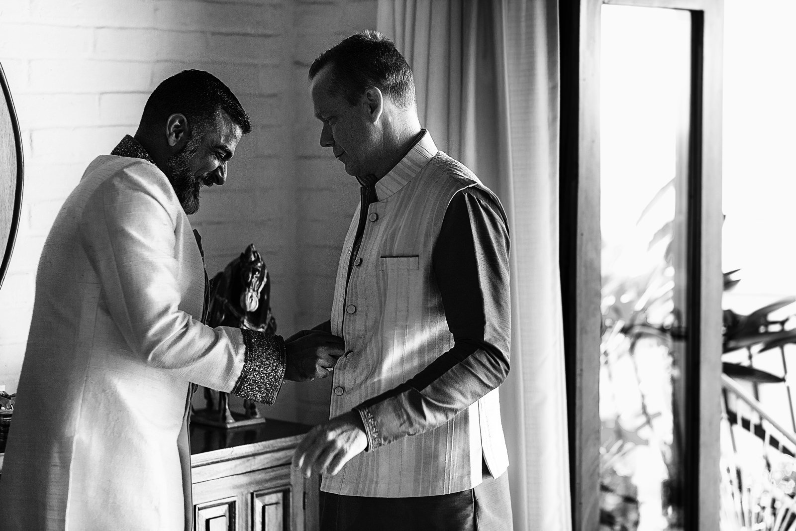 Groom and best man having fun while getting dressed