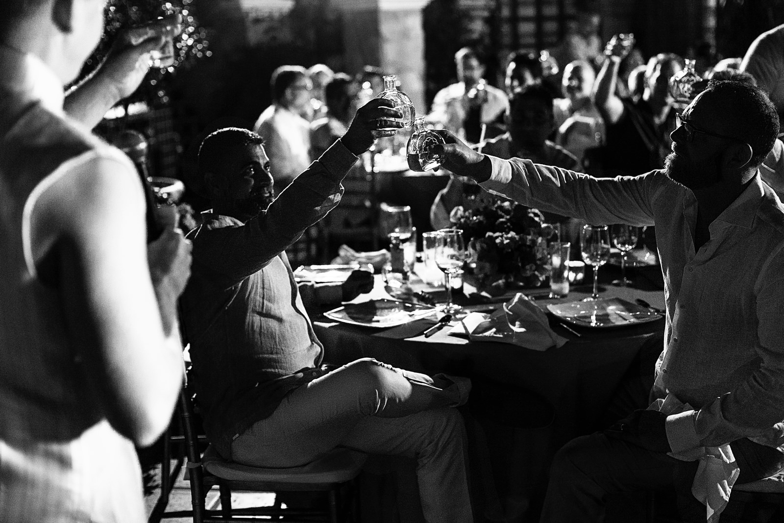Groom and groom raise their bottle of tequila toasting on the best man speech