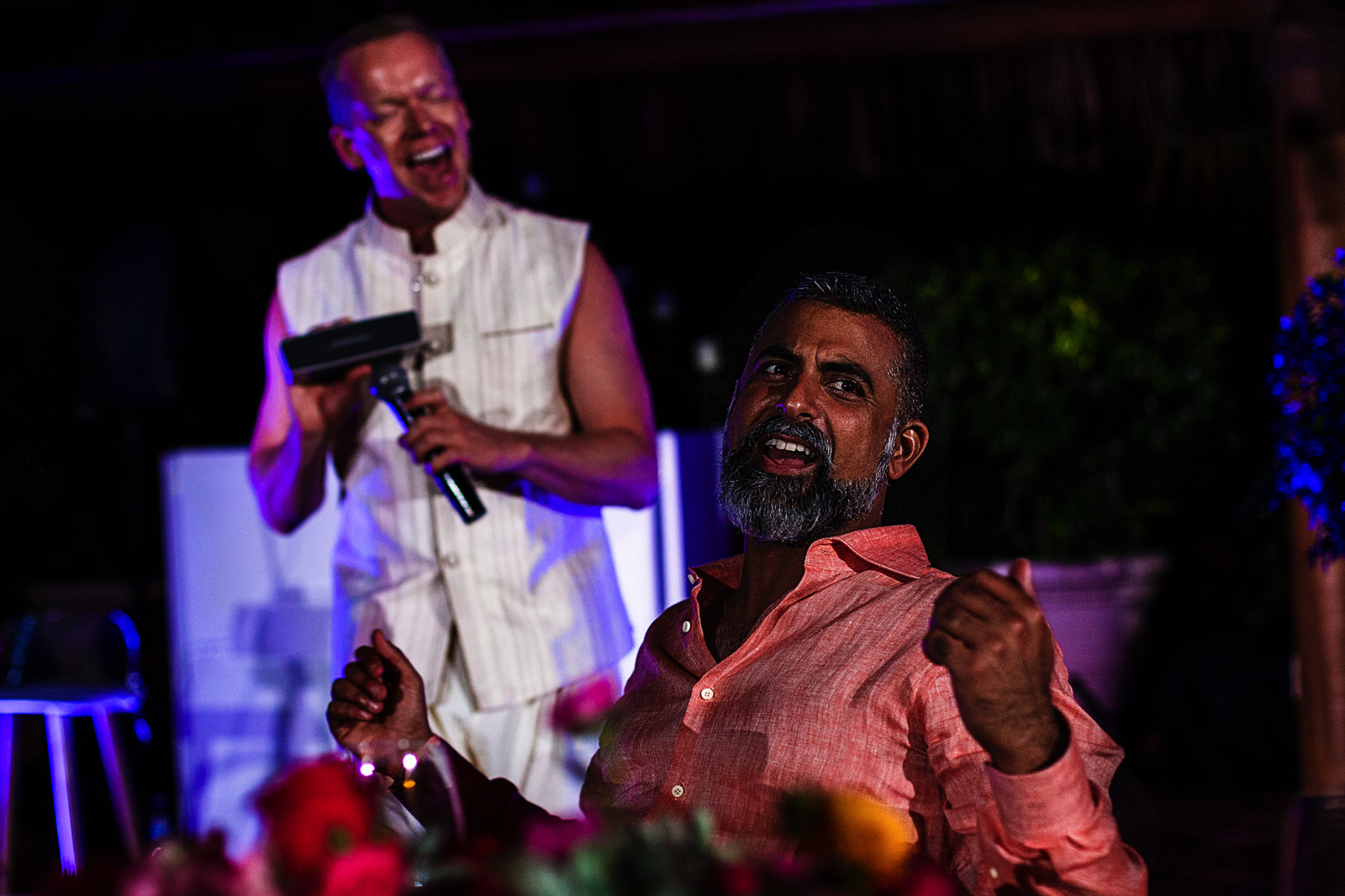 Best man holds a boombox against the microphone on his speech, the groom reacts singing