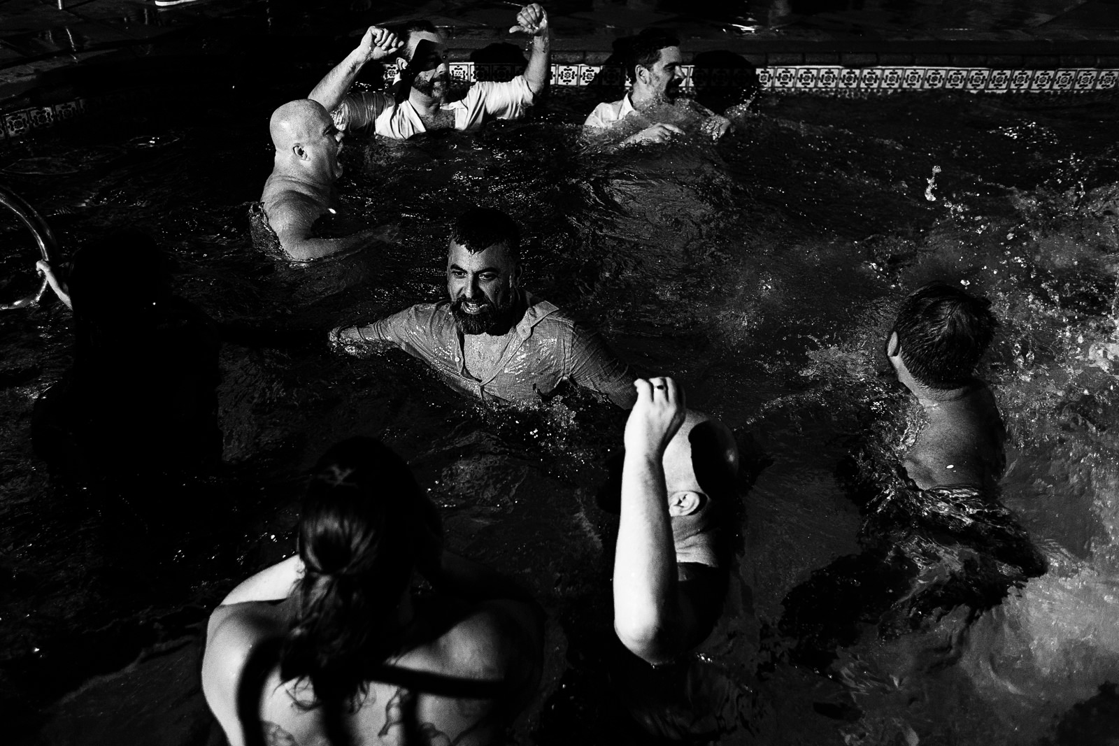 Groom and wedding guests continuing the party in the pool