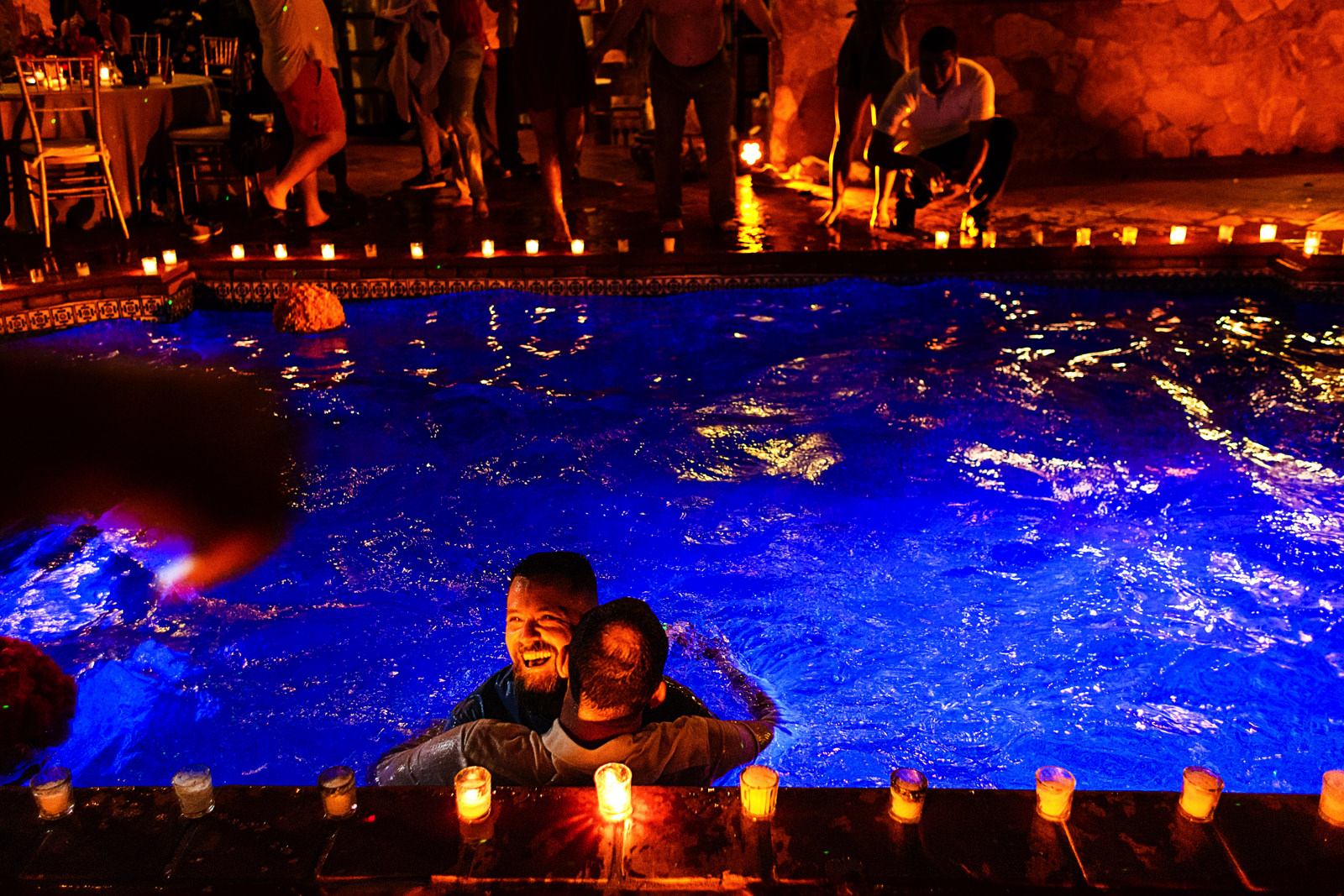 Wedding guest and groom hugging into the Casa Muni's pool