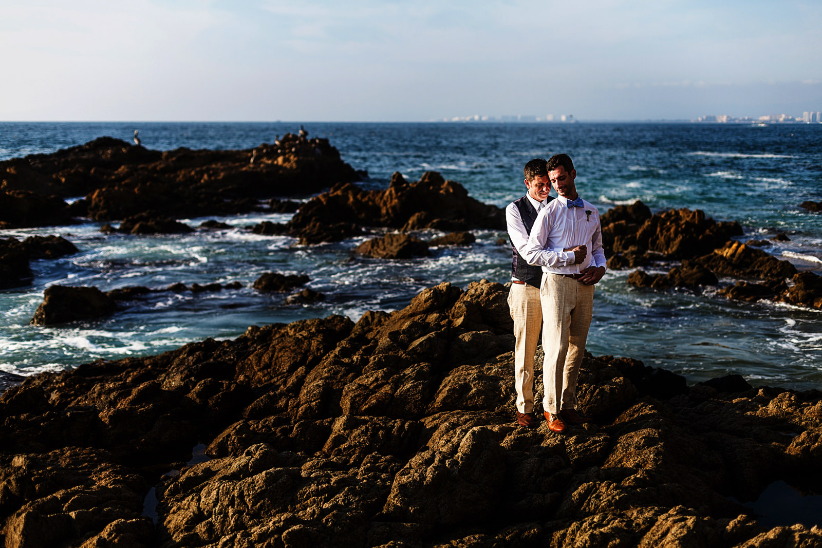 Gay couple portrait standing on the rocks close to the pacific ocean on their destination wedding in Mexico
