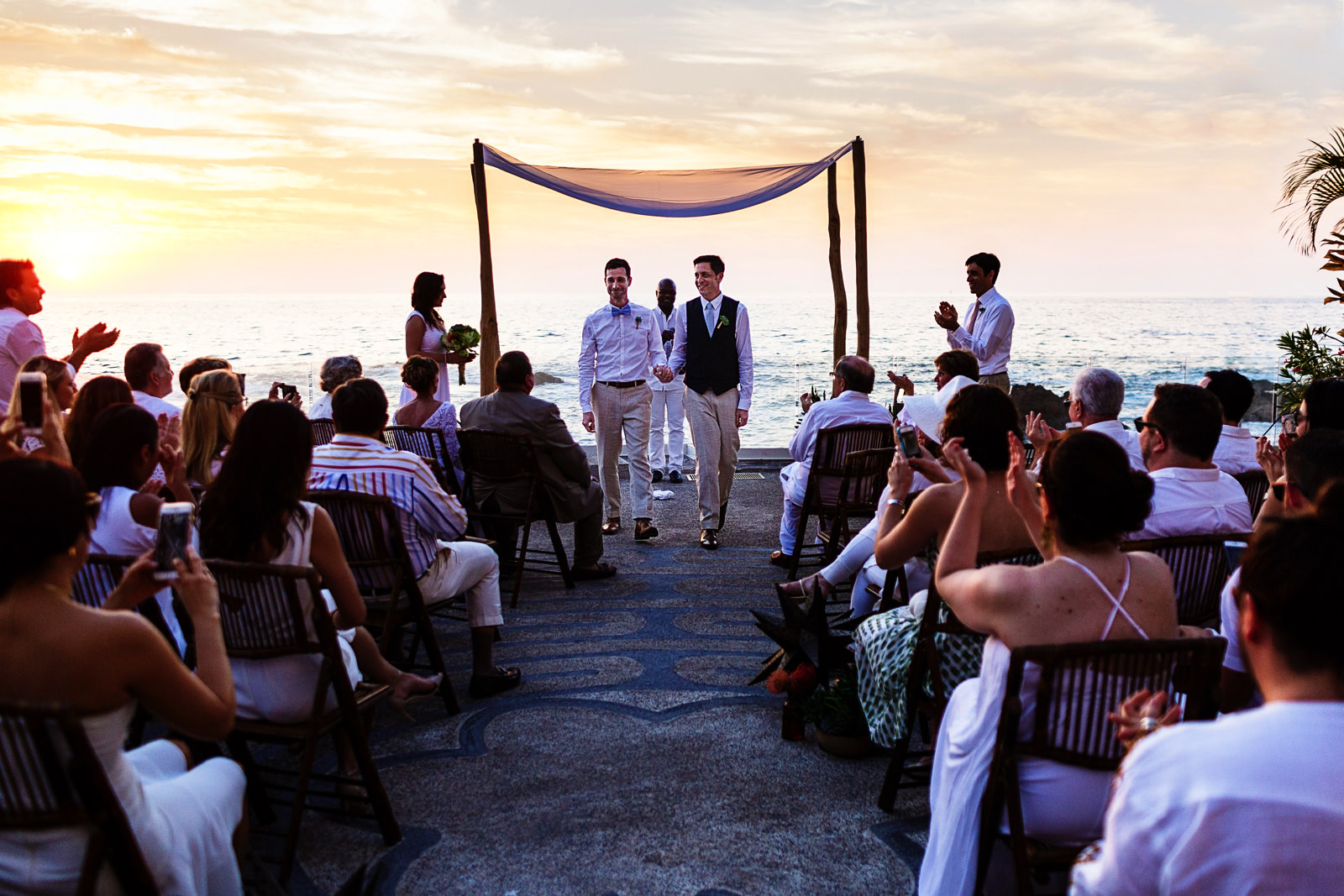 Gay couple exit down the aisle as their ceremony ends with the sunset behind them