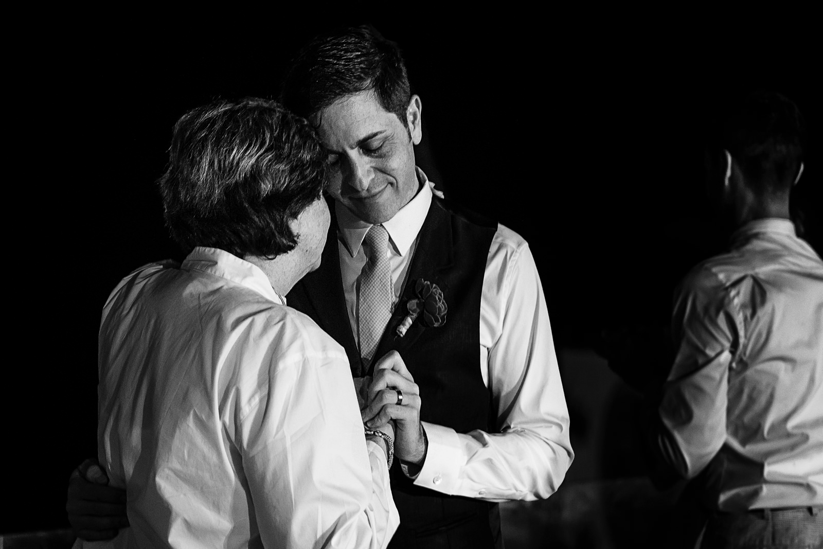 Groom dancing with his mother while gently smiles